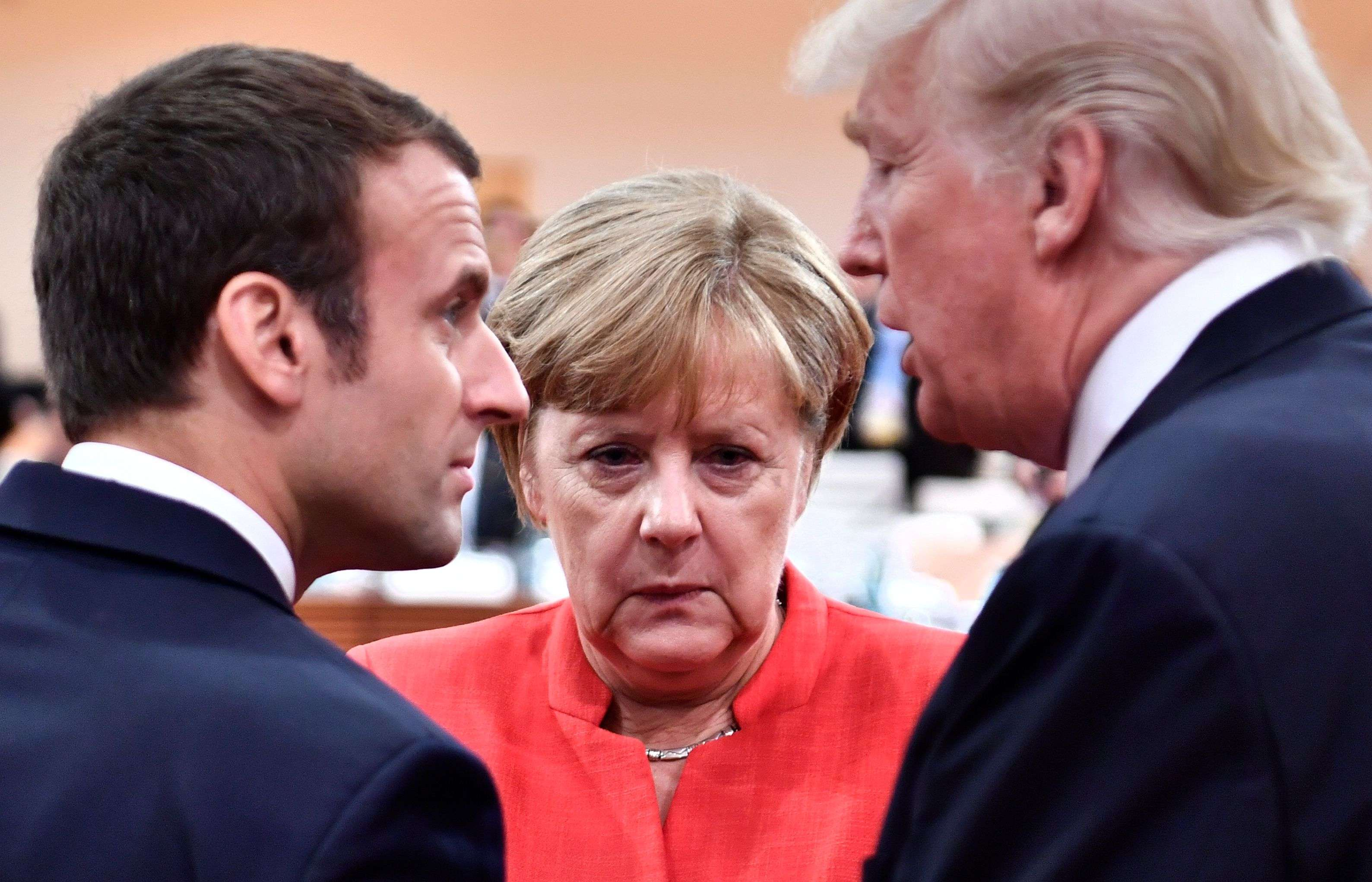 French President Emmanuel Macron (L), German Chancellor Angela Merkel (C) and US President Donald Trump confer at the start of a working session of the G20 meeting in Hamburg, last July. (AFP)
