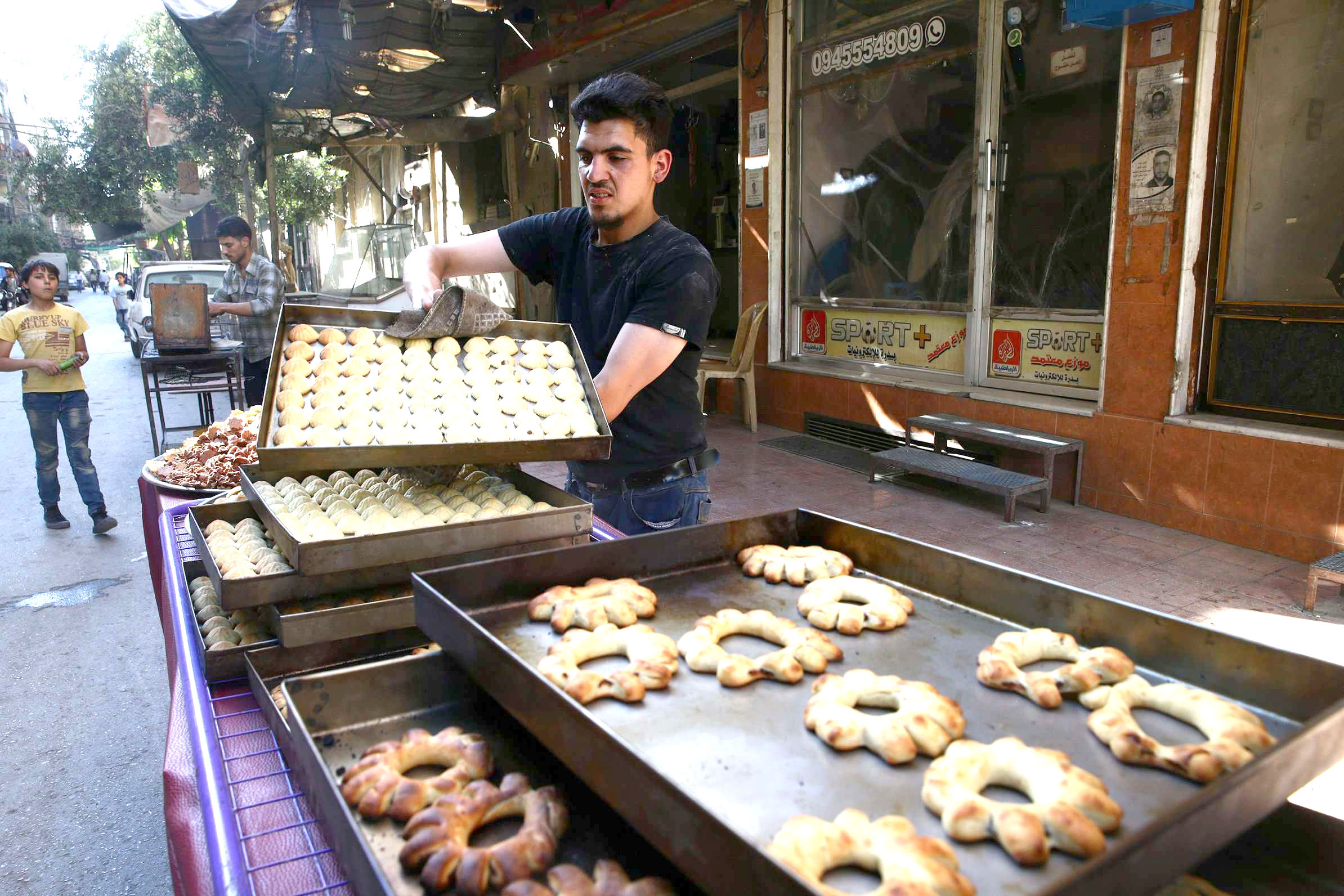 A man arranges sweets to be sold ahead of Ramadan in Douma, the principal town in Eastern Ghouta.                        (Reuters)