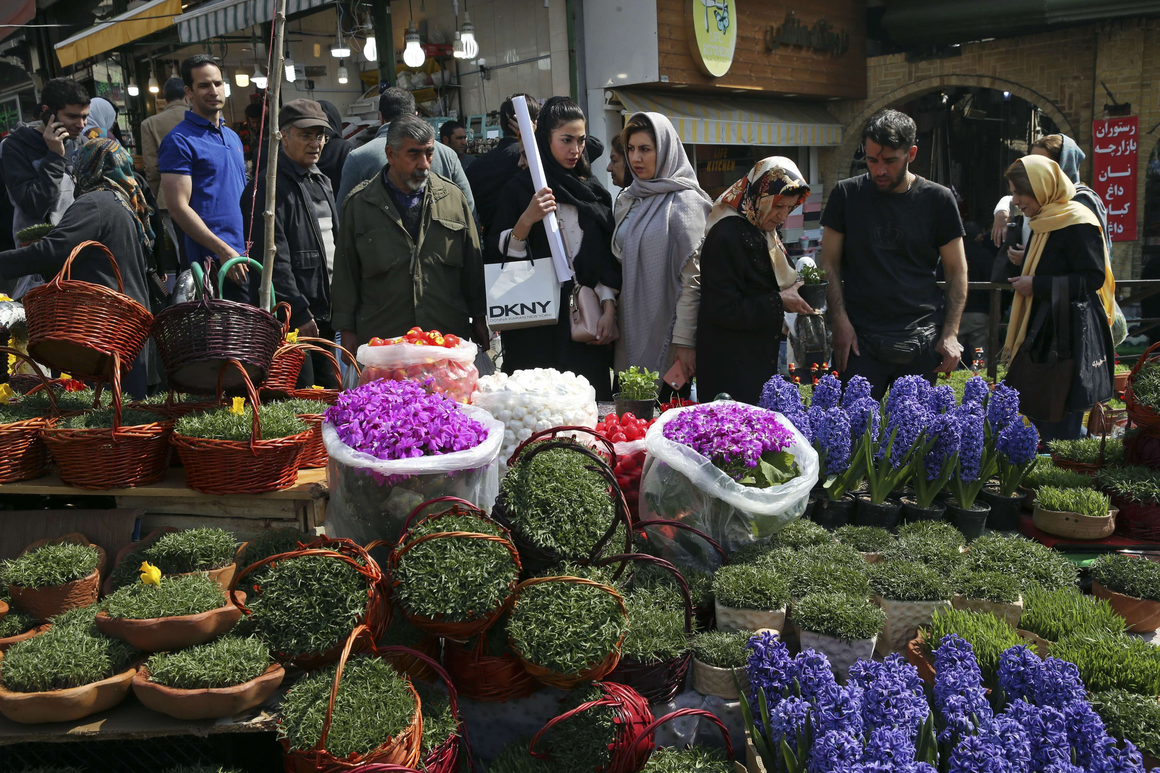 Juggling cultures. Iranians shop for items used to celebrate Noruz at the Tajrish traditional bazaar in northern Tehran. (AP)