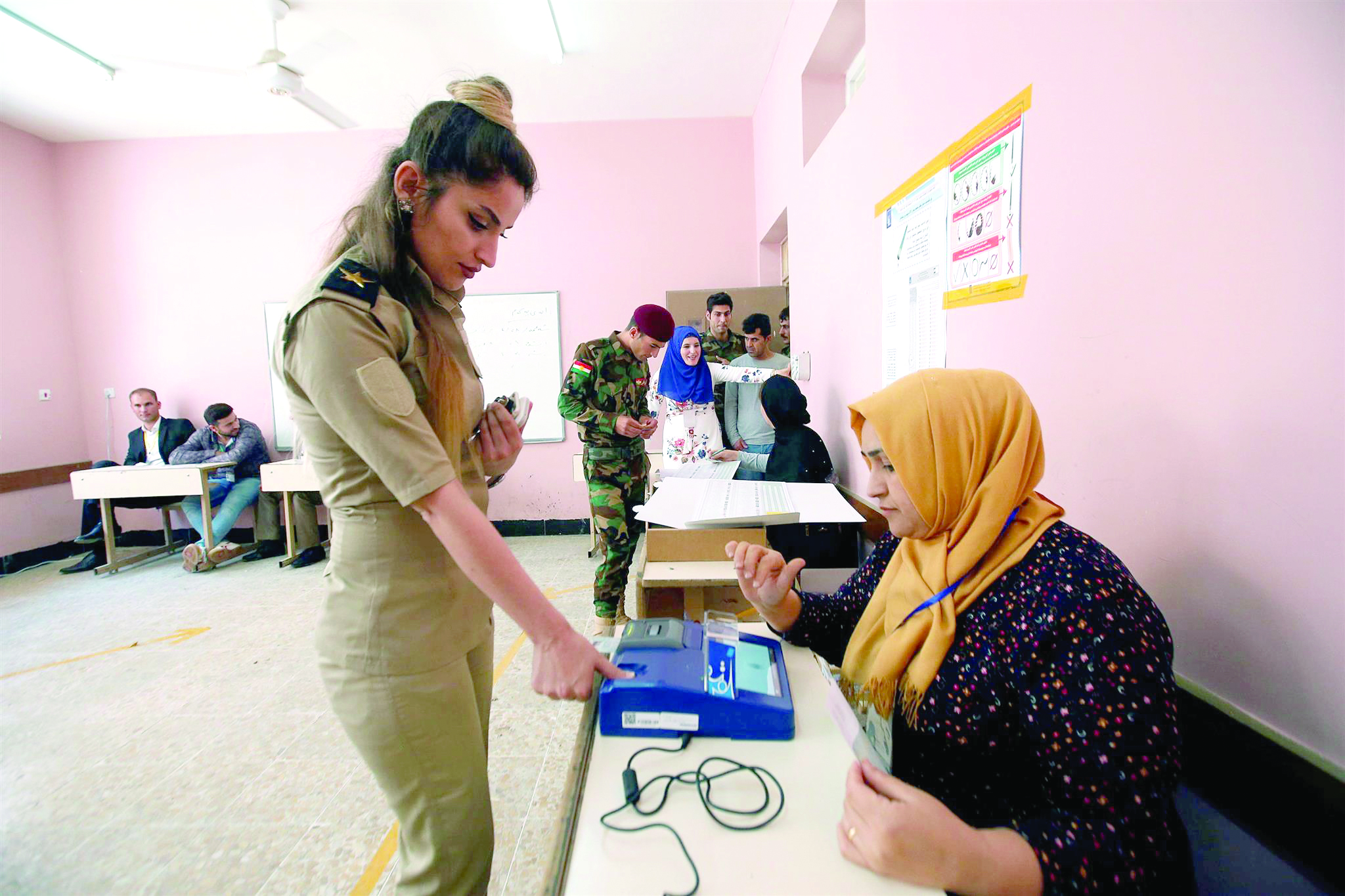 A member of Kurdish peshmerga casts her vote at a polling station two days before polls open to the public in Erbil, on May 10. (Reuters)