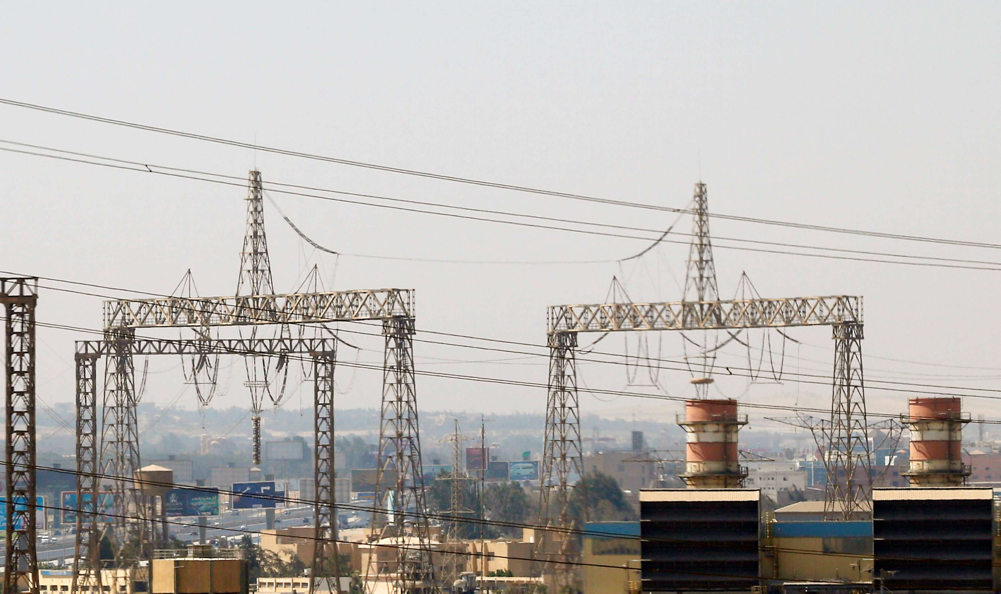Electricity pylons and power transmission lines are seen along a road in Cairo.    (Reuters)