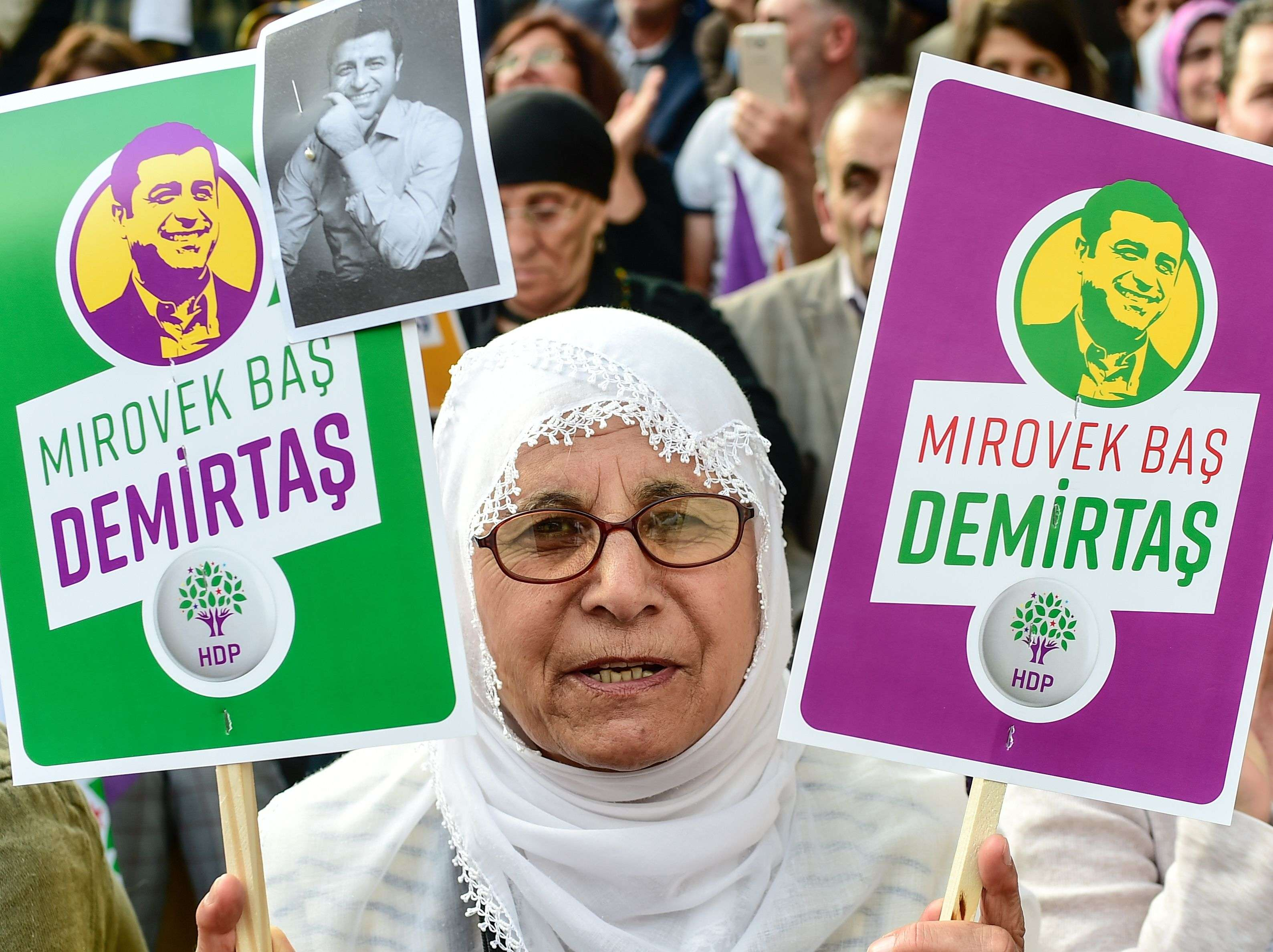 A woman holds pictures of former HDP leader Selahattin Demirtas, in jail for a year and a half, during a rally, on May 4. (AFP)