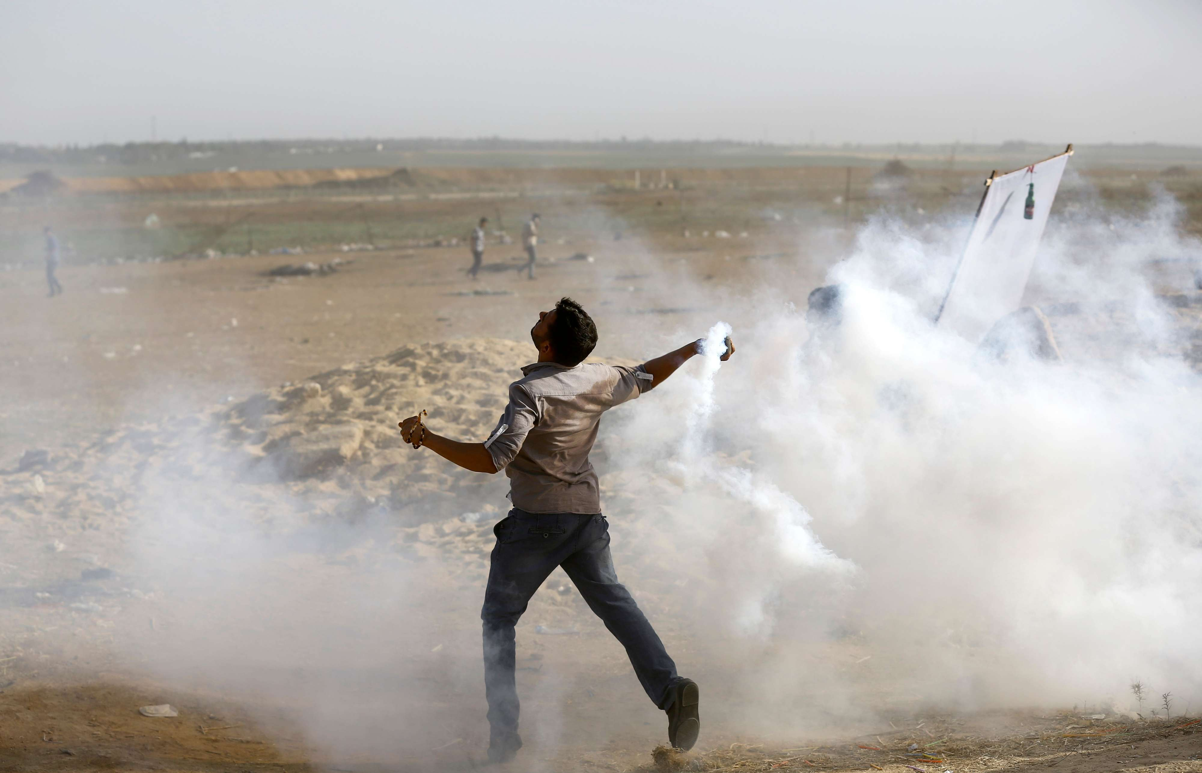 A Palestinian man throws back an Israeli tear gas canister during protests near the Gaza-Israel the border, on May 18. (AFP)