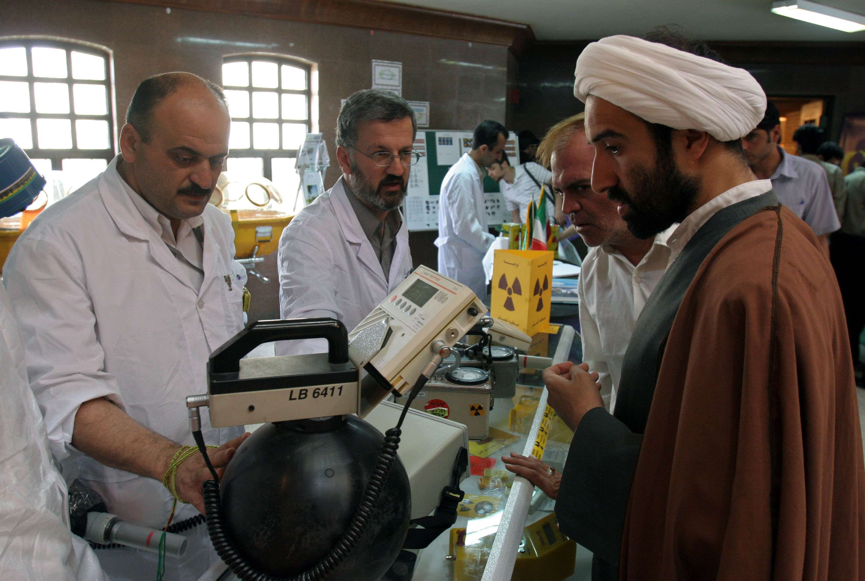 Endless boasting. Iranian technicians explain a piece of equipment to a clergyman during an exhibition at the Qom University, on May 2. (AP)