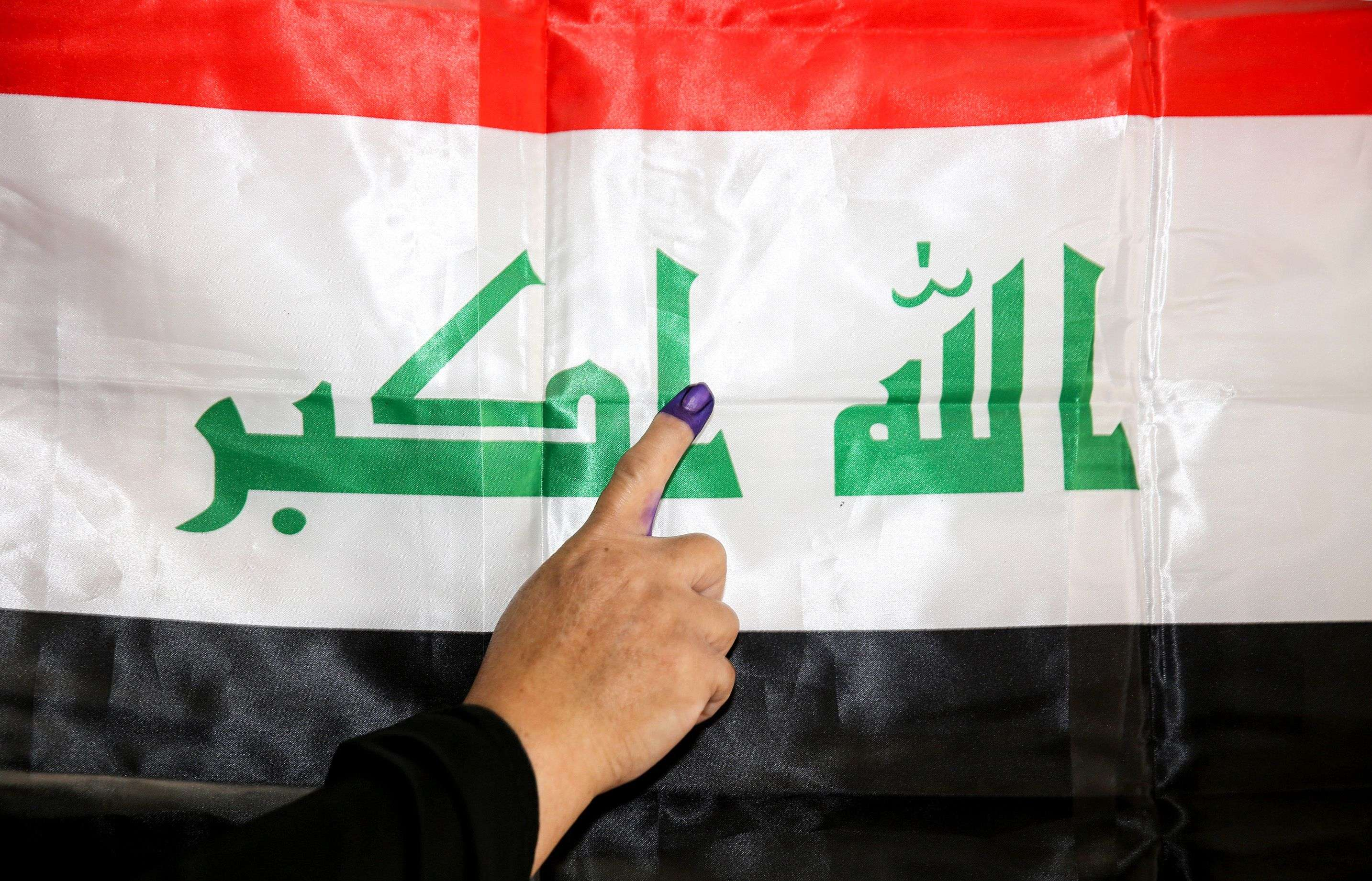 An Iraqi woman shows her ink-stained index finger before a national flag after having cast her vote in the country's parliamentary election, in the capital Baghdad's Karrada district on May 12. (AFP)