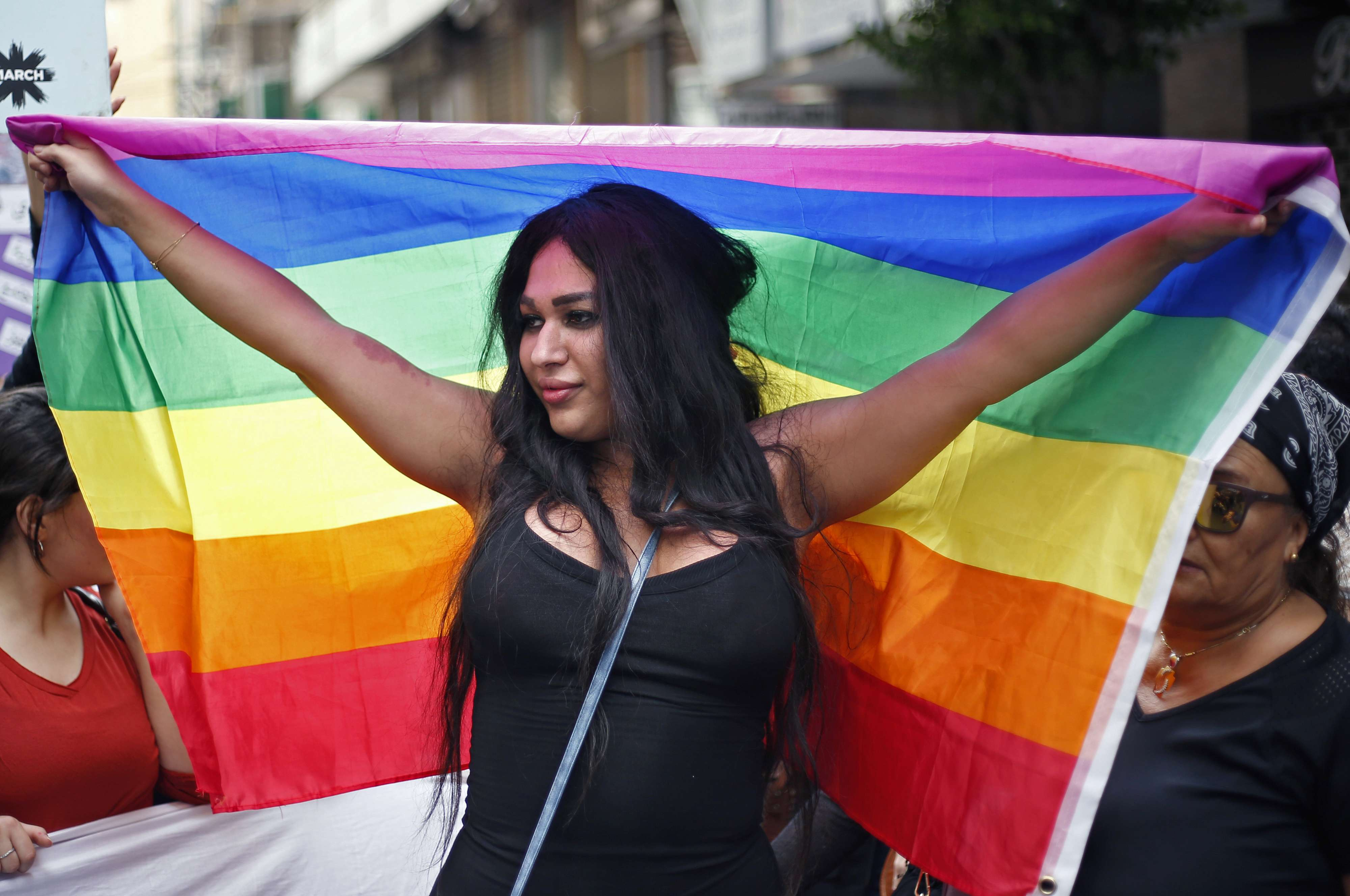 A woman holds a rainbow flag of the LGBT movement as she marches in Beirut, on March 11. (AP)