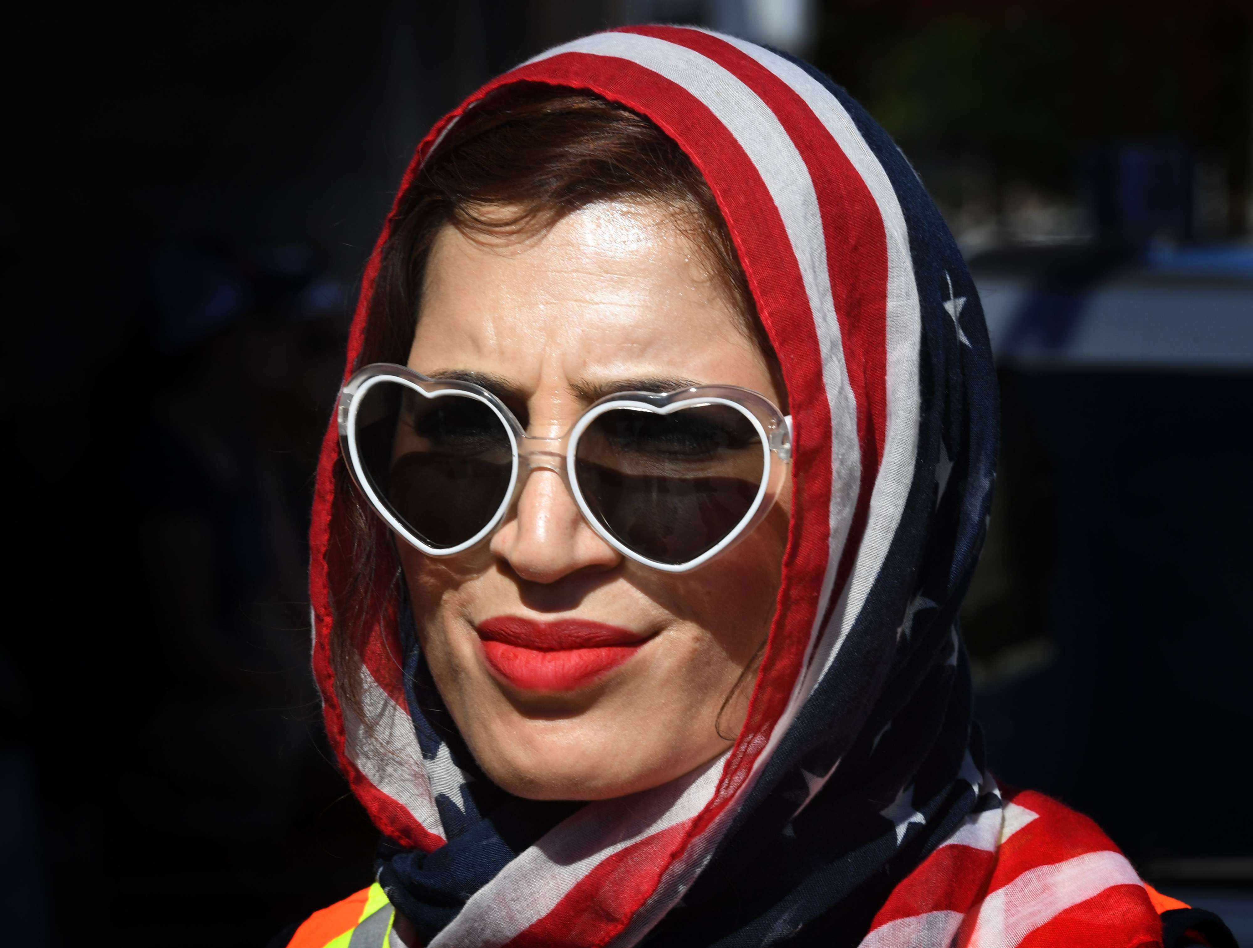 A woman wears an American flag for a headscarf as she participates in the '#NoMuslimBanEver' rally in downtown Los Angeles, California last year. (AFP)