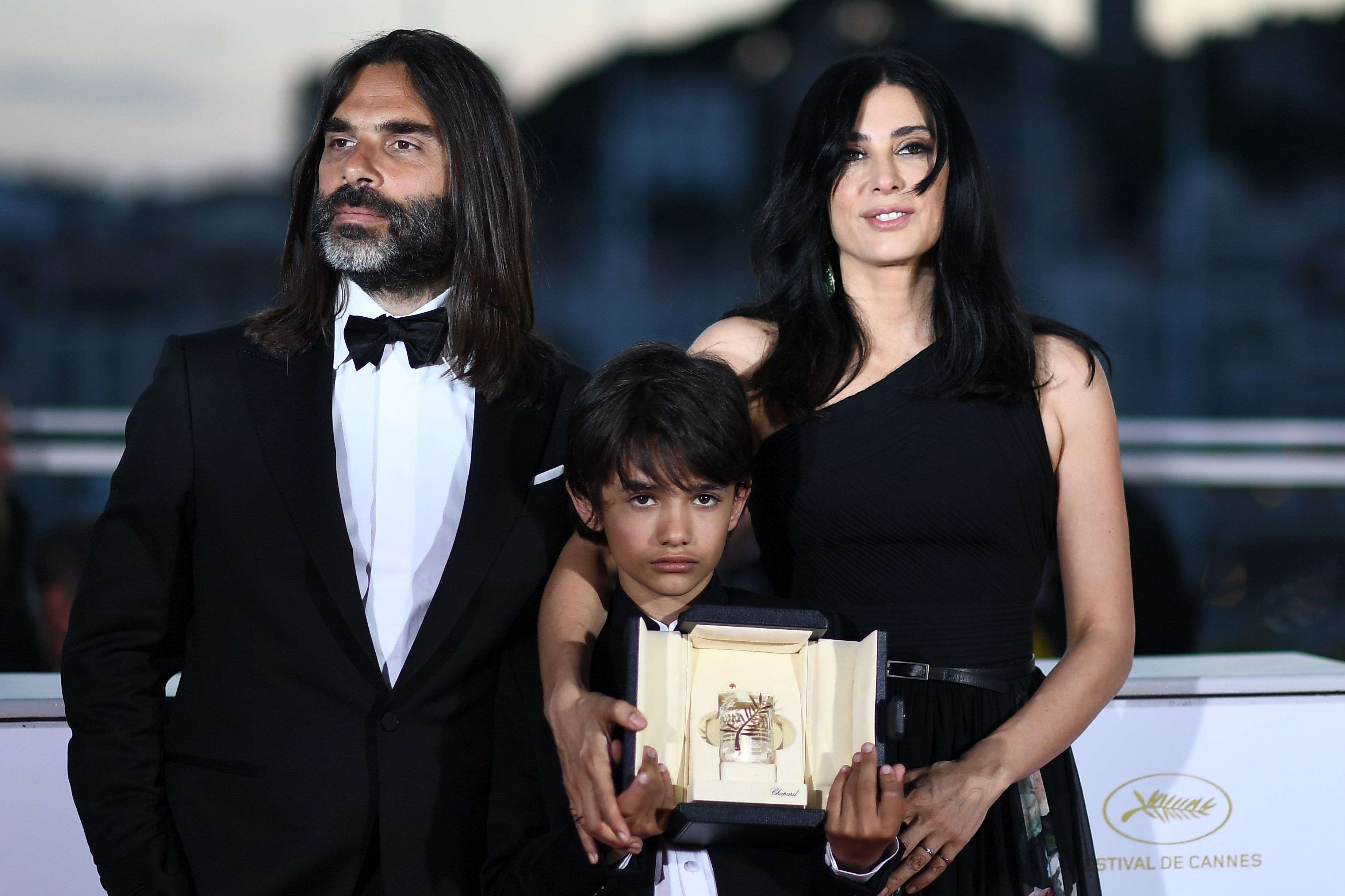 "Lebanese director and actress Nadine Labaki (R), her husband Lebanese producer Khaled Mouzanar (L) and Syrian actor Zain al-Rafeea pose with the trophy she won for the film ""Capharnaum"" at the 71st edition of the Cannes Film Festival, on May 19. (AFP)"