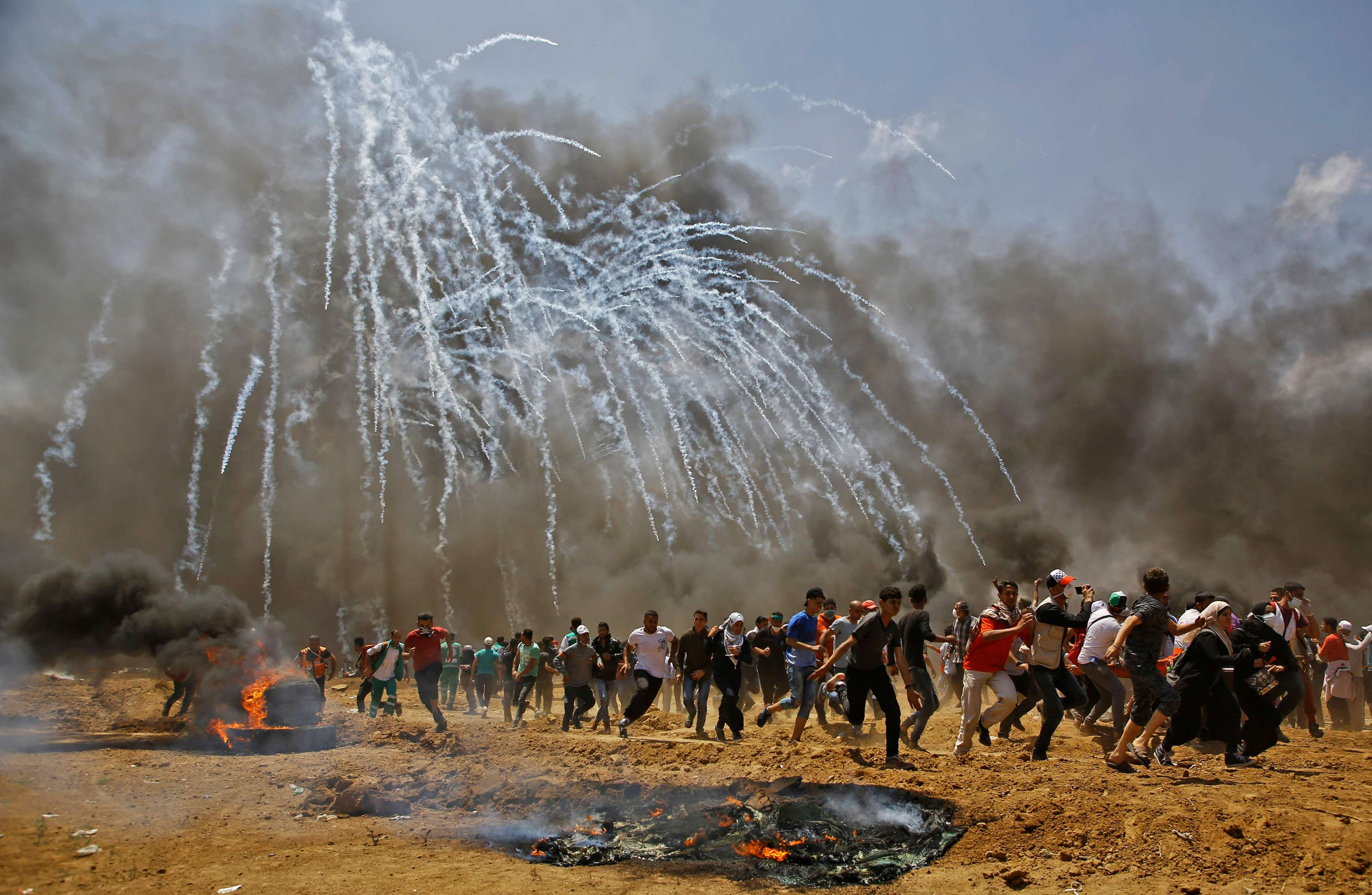Palestinians run for cover from Israeli tear gas near the border between Israel and the Gaza Strip, on May 14. (AFP)