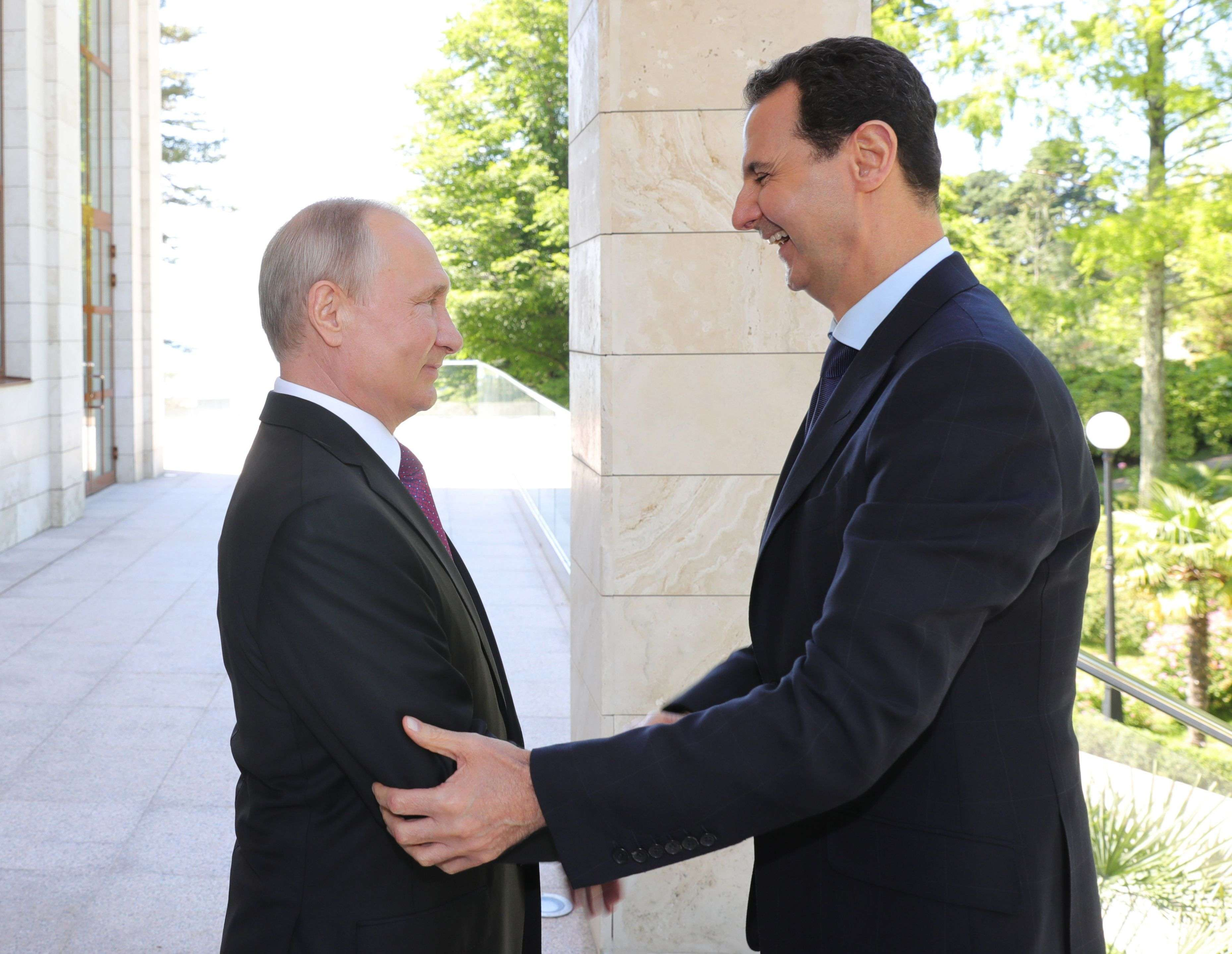 Russian President Vladimir Putin (L) welcomes Syrian President Bashar Assad during in the Black Sea resort of Sochi, on May 17. (AP)