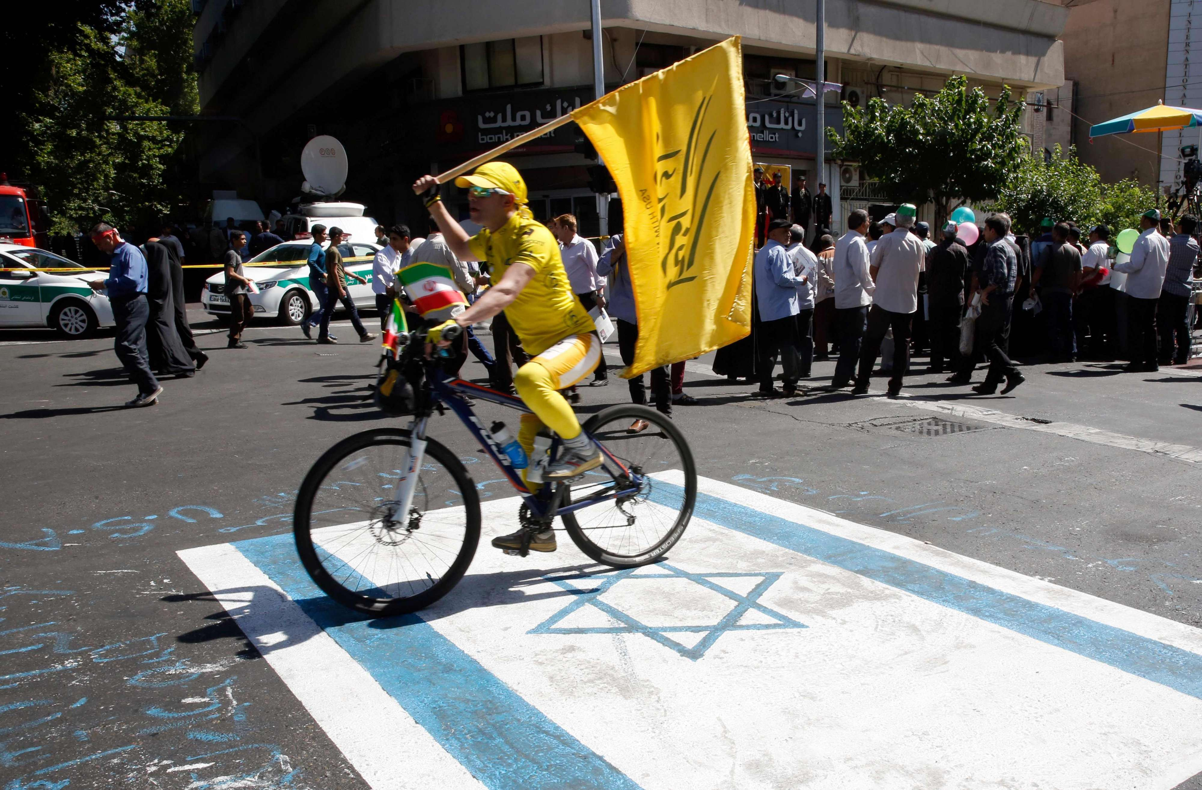 An Iranian man rides his bicycle across a reproduction of an Israeli flag painted on a street in Tehran. (AFP)