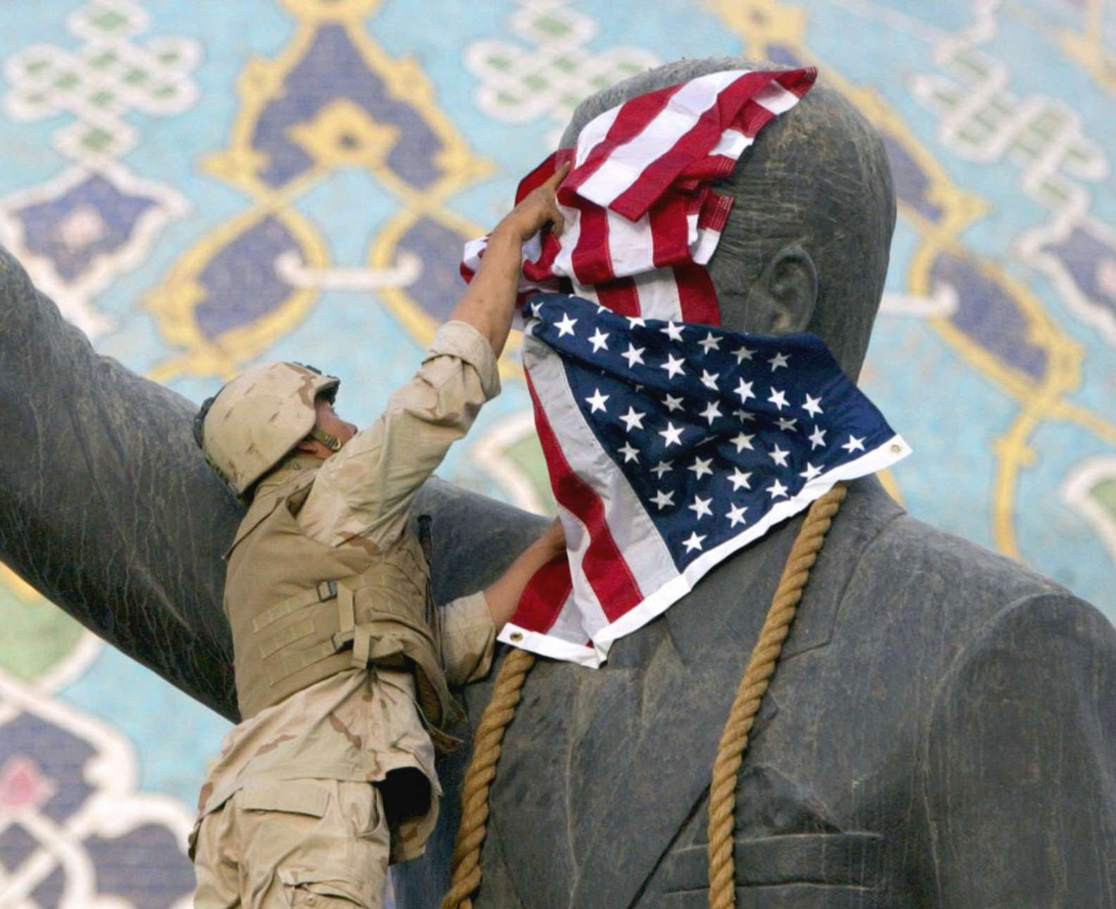 A file photo showing a US Marine covers the face of a statue of then Iraqi President Saddam Hussein with a US flag in Baghdad, on April 9, 2003. (AP)