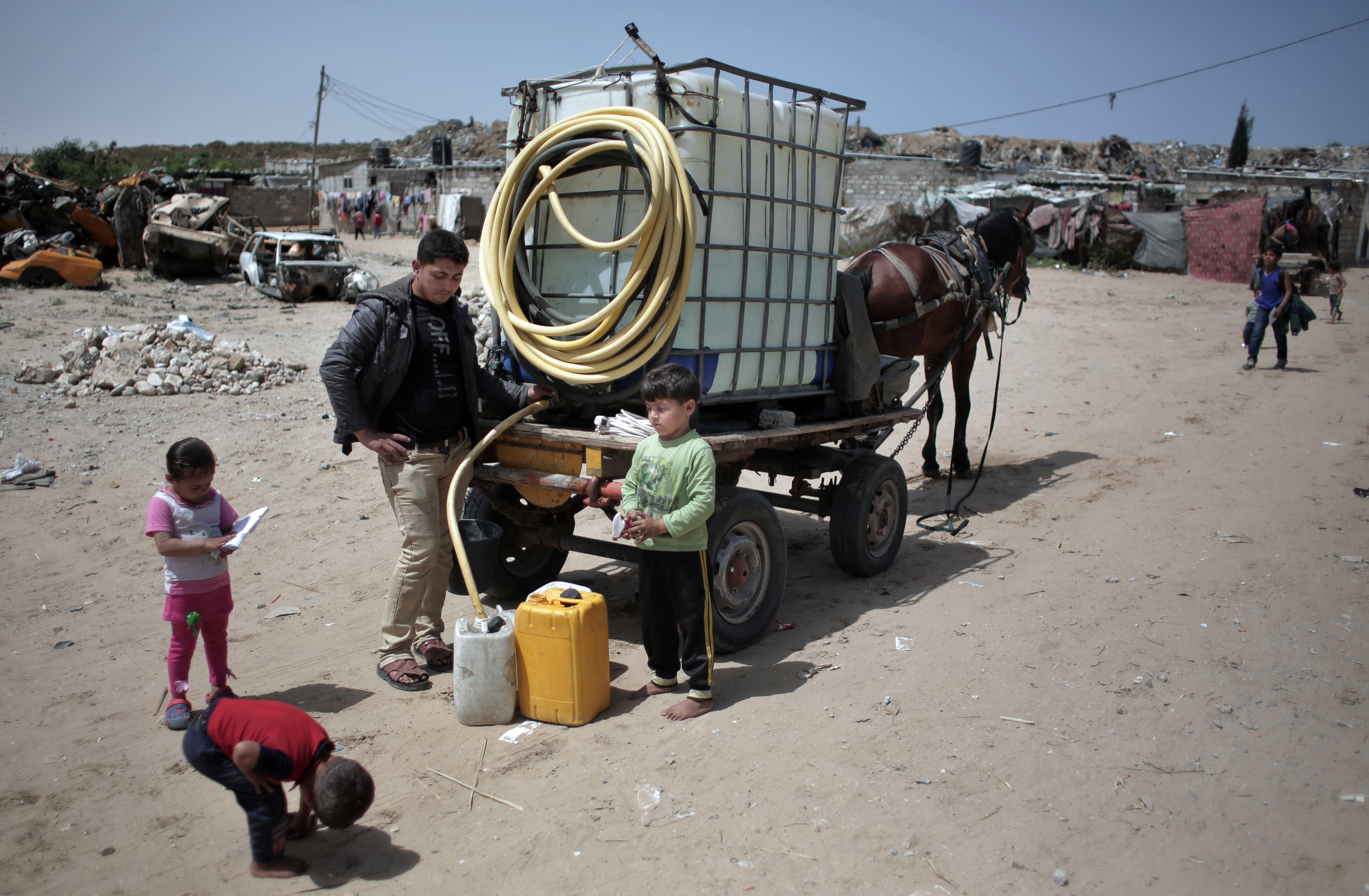 Low share. Palestinian children fill plastic gallons with drinking water from a vendor in Khan Younis. (AP)