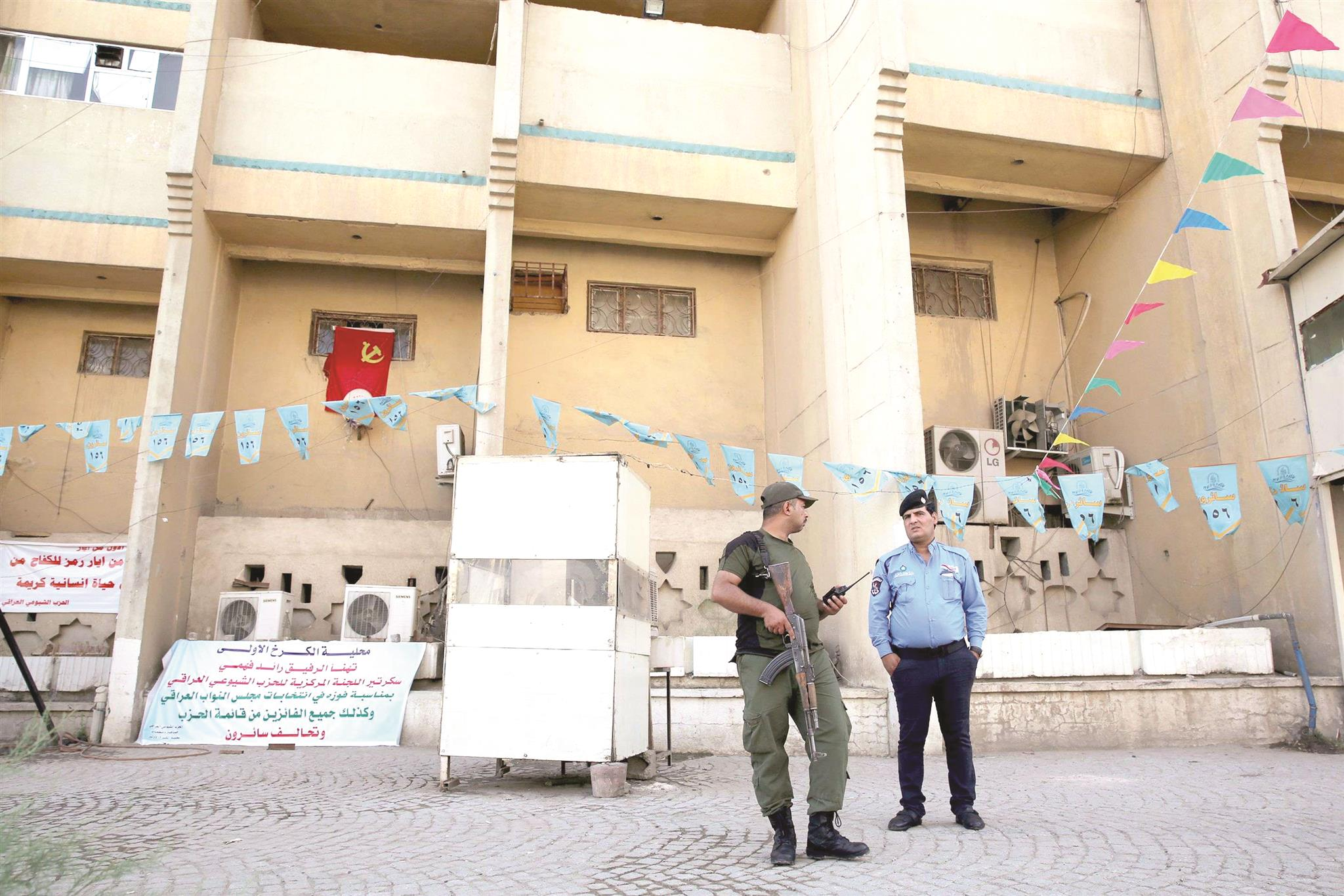 An Iraqi policeman and a soldier stand guard before the headquarters of the Iraqi Communist Party after two bombs exploded in Baghdad, on May 26. (AFP)
