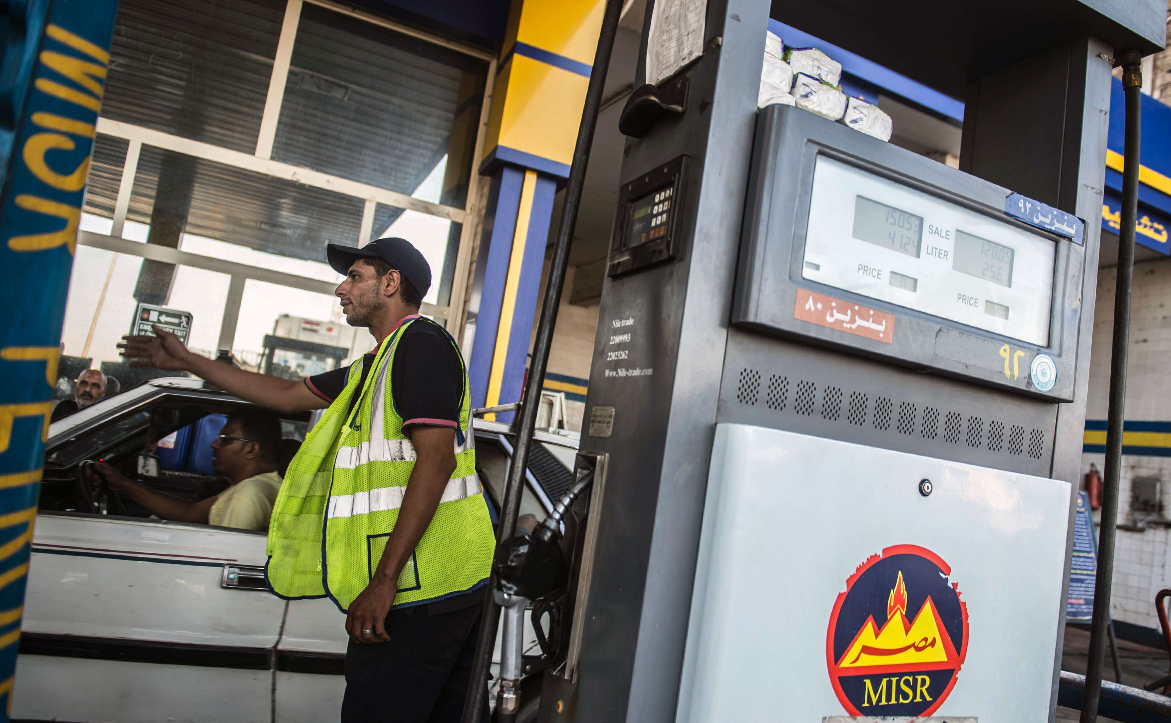 A worker gestures for cars to move as others fill up at a petrol station in Cairo. (AFP)