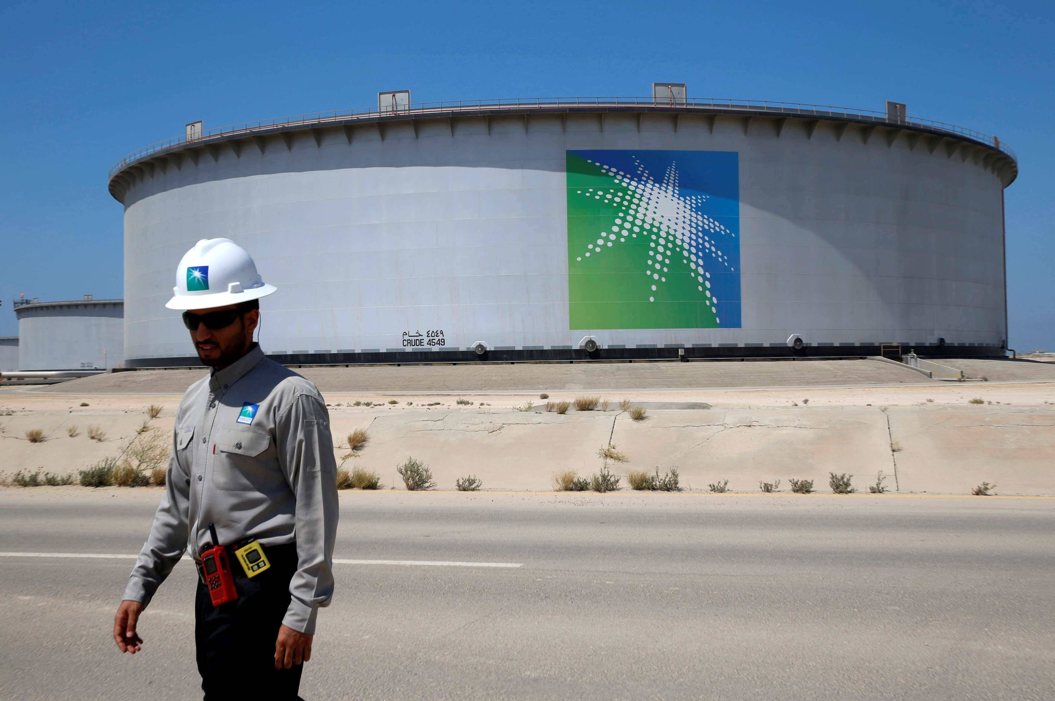Restructuring the core. An Aramco employee walks near an oil tank at Saudi Aramco's Ras Tanura oil refinery, on May 21.                   (Reuters)