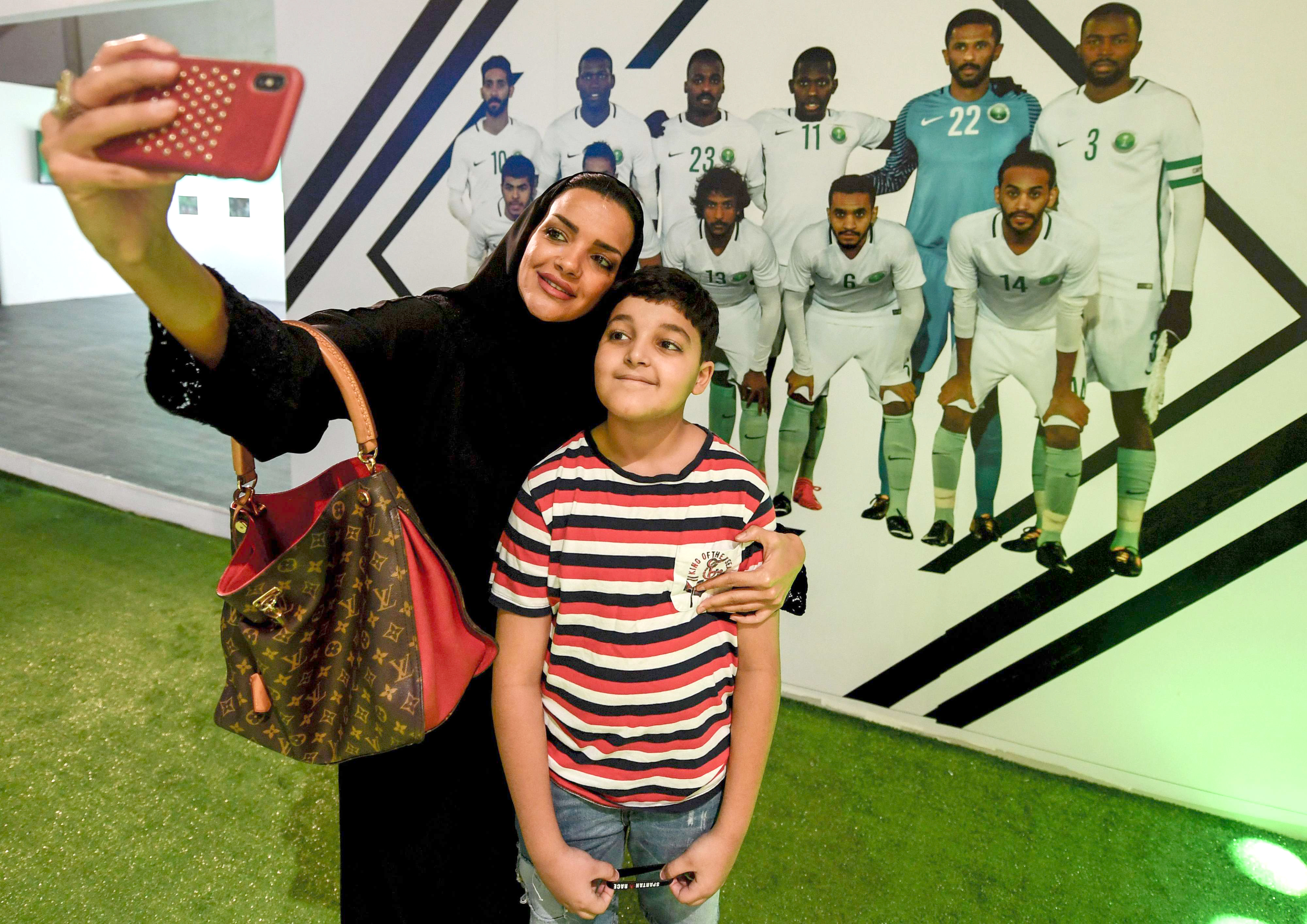 "A Saudi woman and boy pose for a ""selfie"" before a wall showing a picture of the Saudi national football team in Jeddah, on June 14. (AFP)"