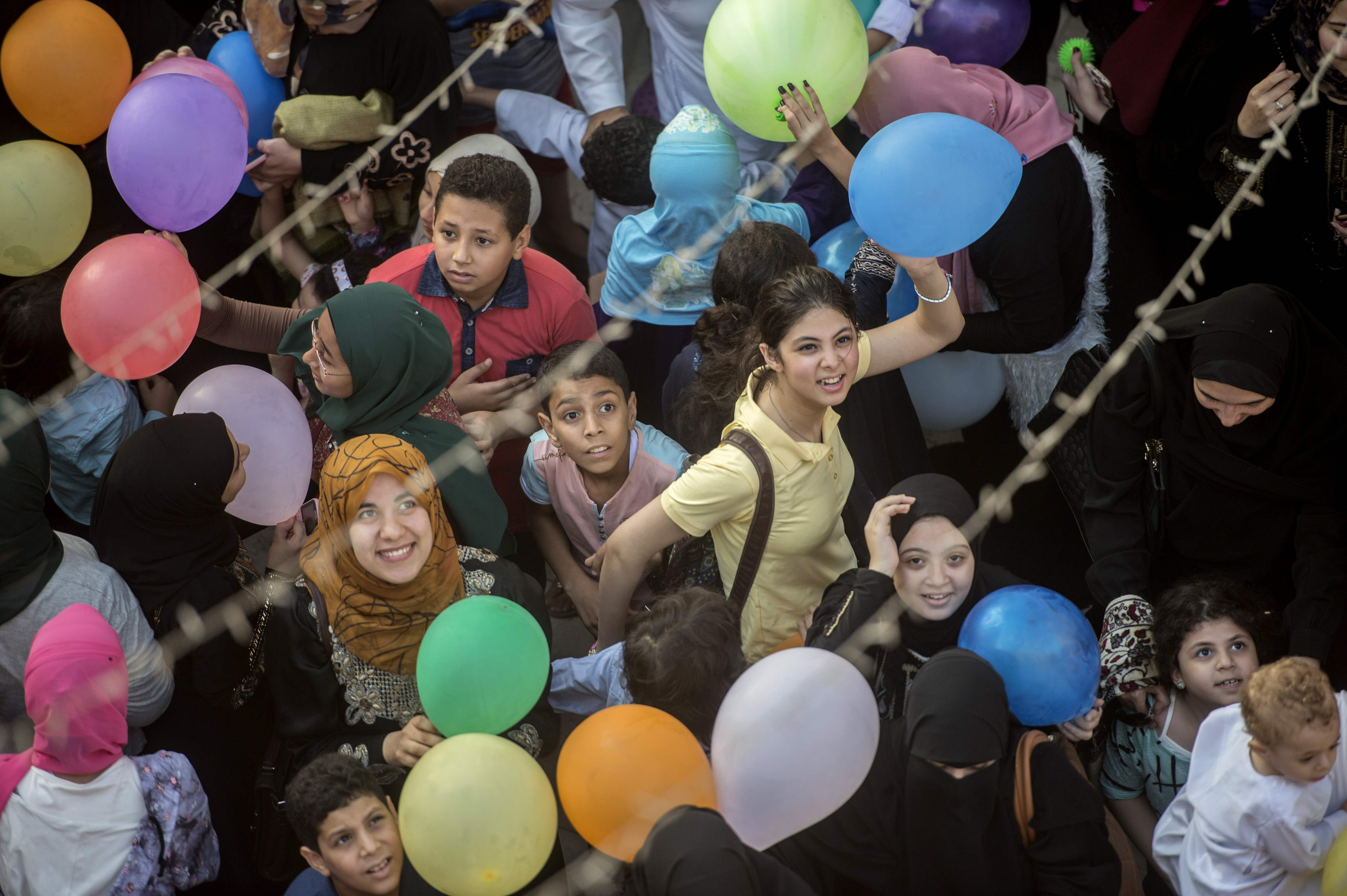 Egyptians look up as balloons are released from the roof of a mosque on Eid al-Fitr. (AFP)