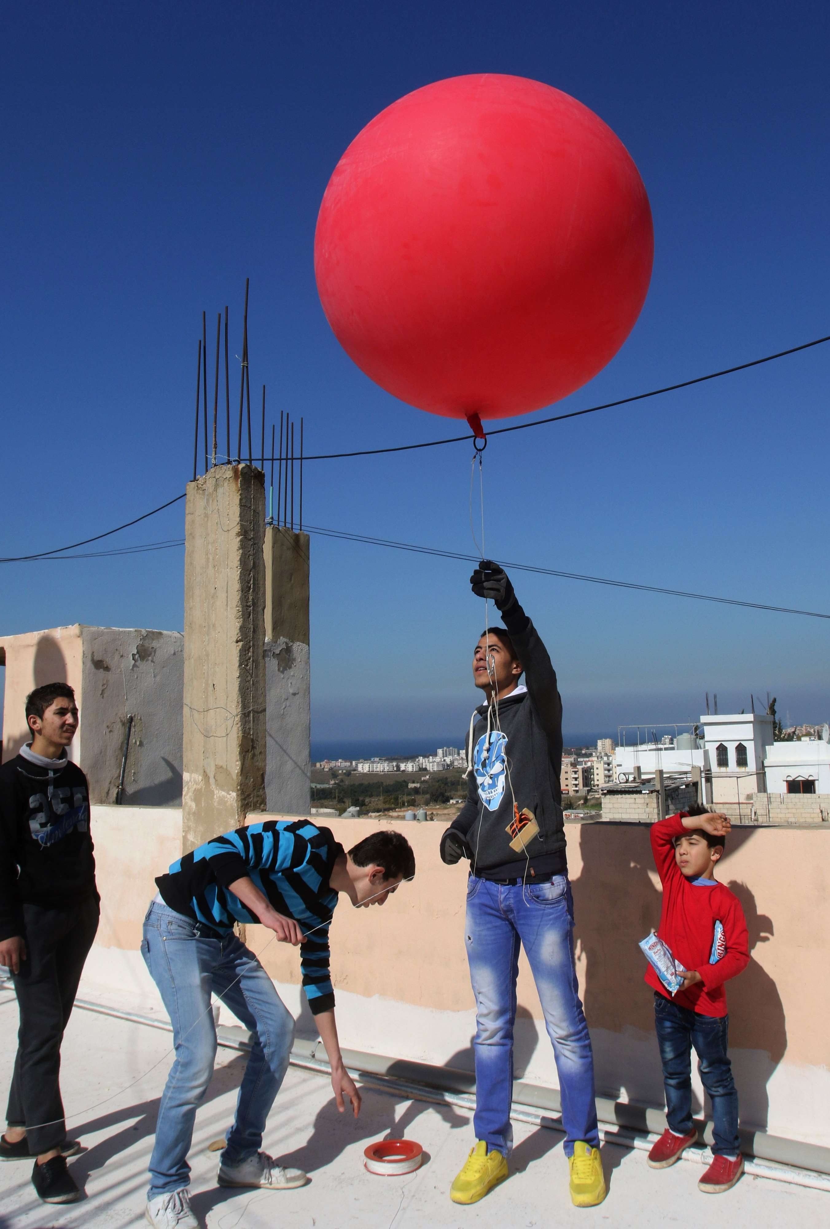 Keeping hope alive. Palestinian refugees fix a camera on a helium balloon before flying it over different parts of the Burj al-Shamali refugee camp in southern of Lebanon. (AFP)