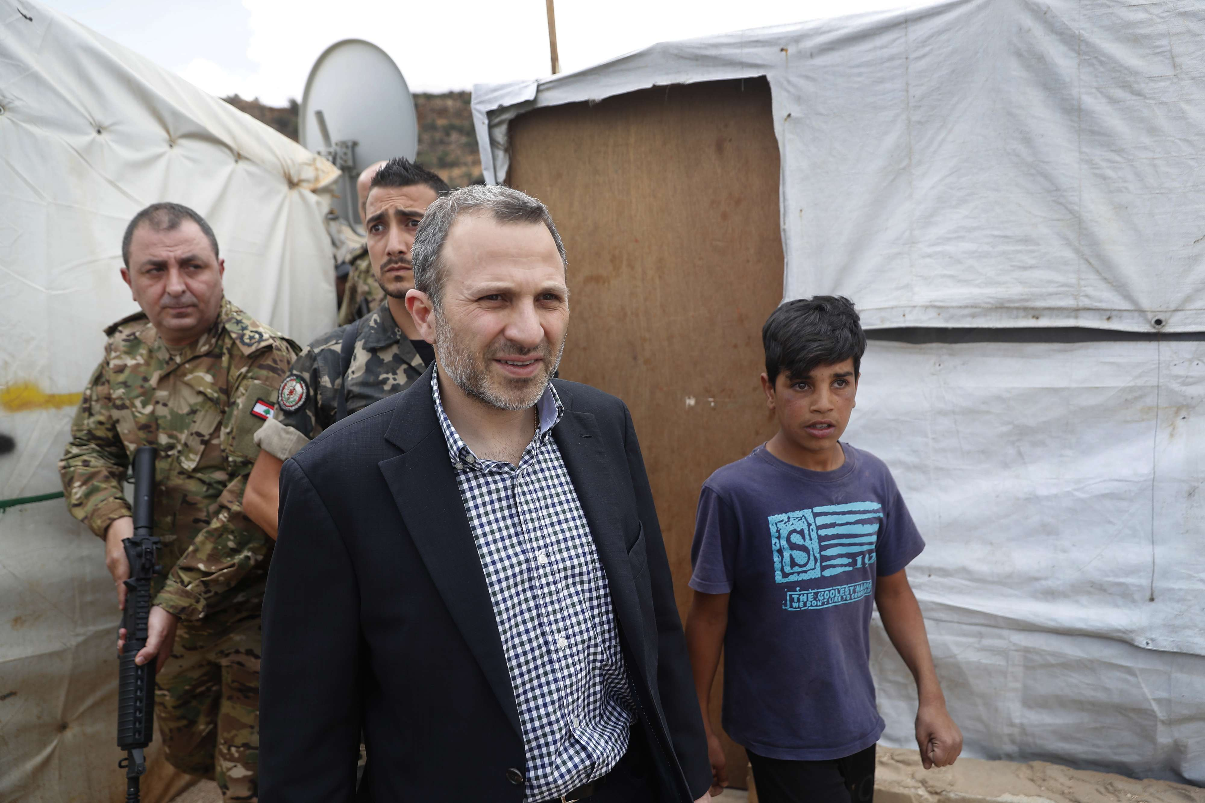 Populist approach. Lebanese Foreign Minister Gibran Bassil, escorted by Lebanese soldiers, visits a Syrian refugee camp in Arsal, on June 13. (AP)