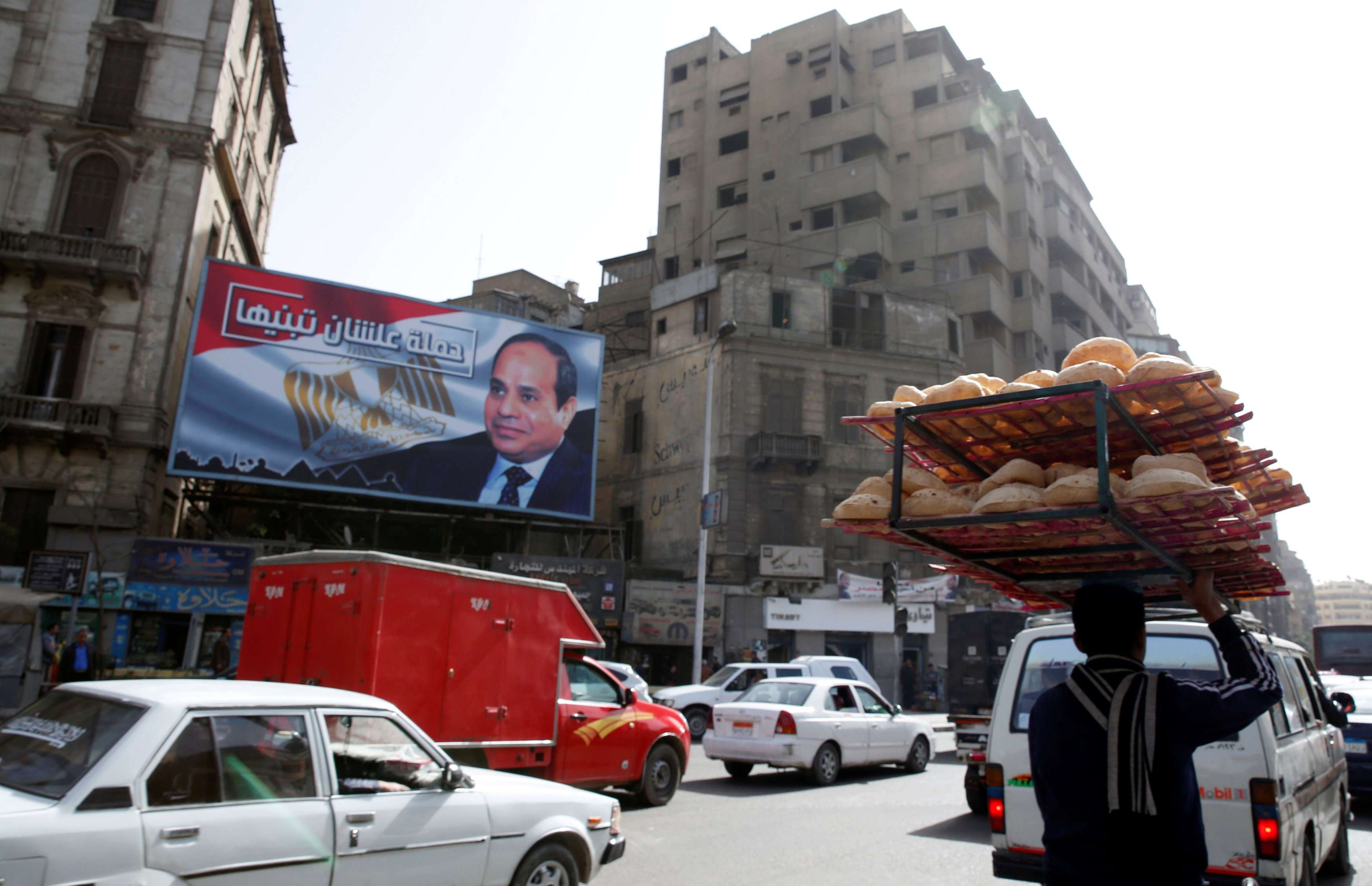 A man carries bread along a busy street near a poster of Egypt's President Abdel Fattah al-Sisi in Cairo. (Reuters)