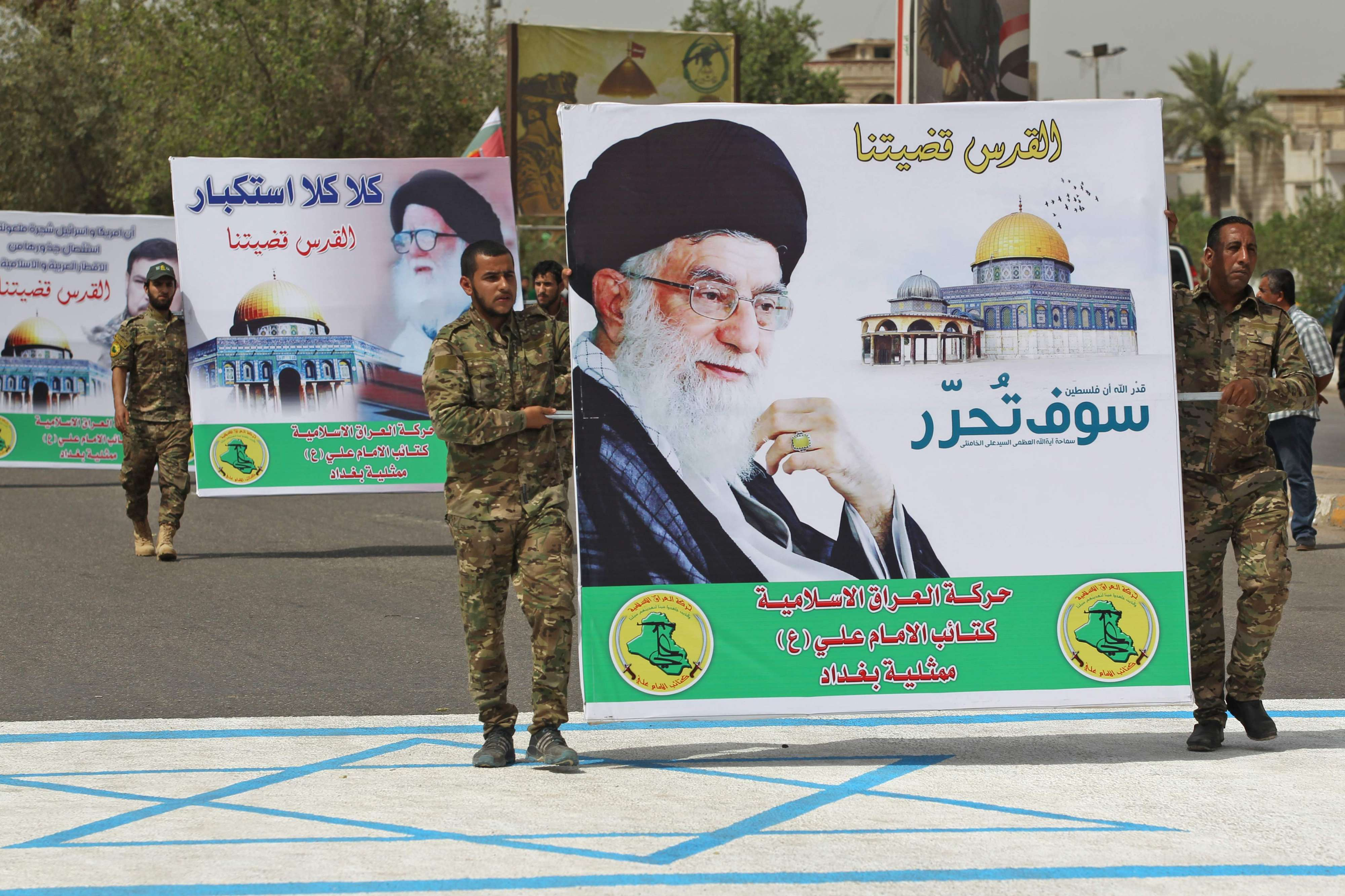 "Far-fetched theatrics. Shia fighters carry a poster of Iran's Supreme Leader Ayatollah Ali Khamenei during a rally to mark ""Quds day"" in Baghdad, on June 8. (AFP)"