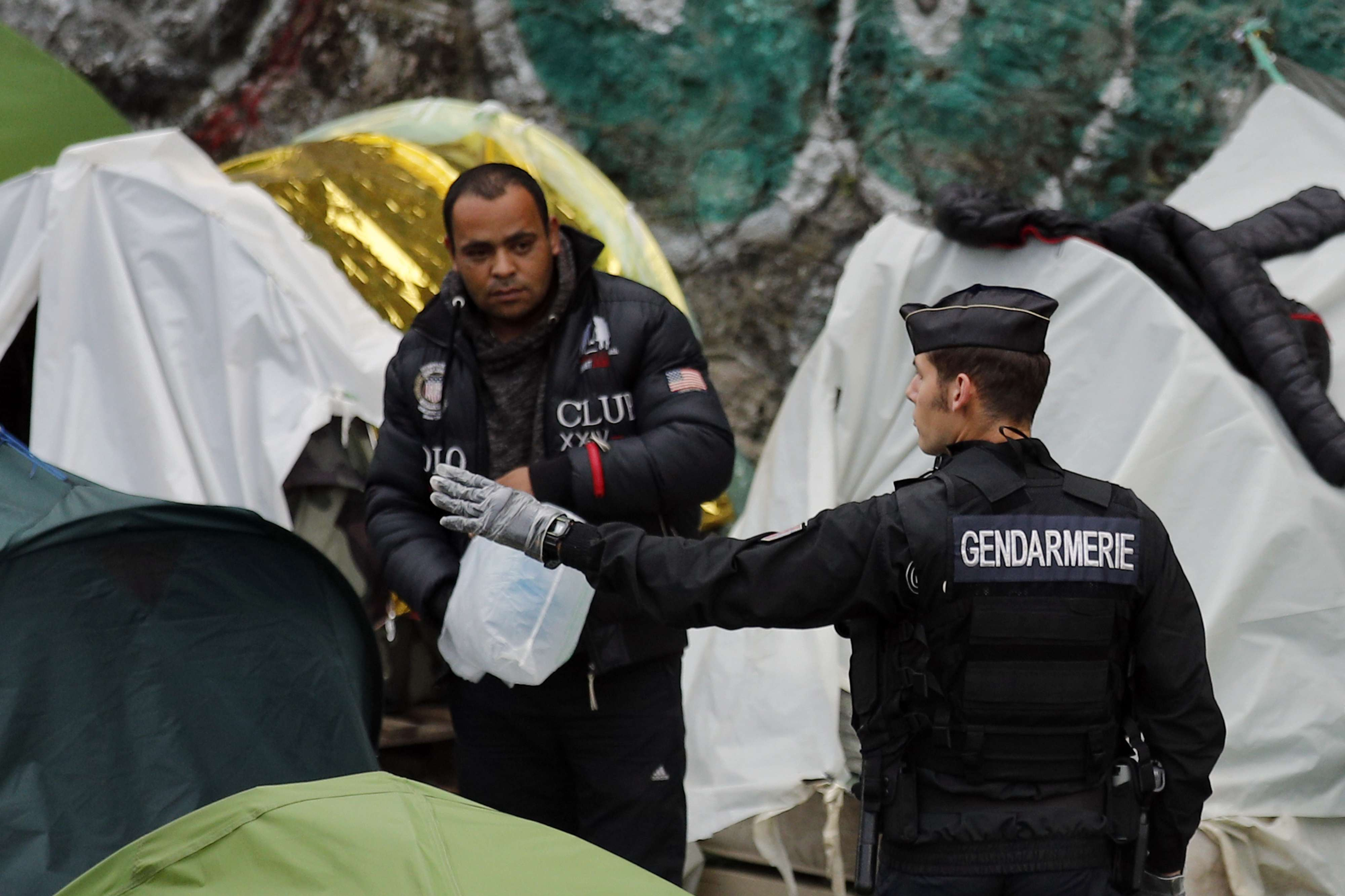 A French gendarme gestures to a migrant during a clearing out of a makeshift camp in central Paris, on June 4. (AP)