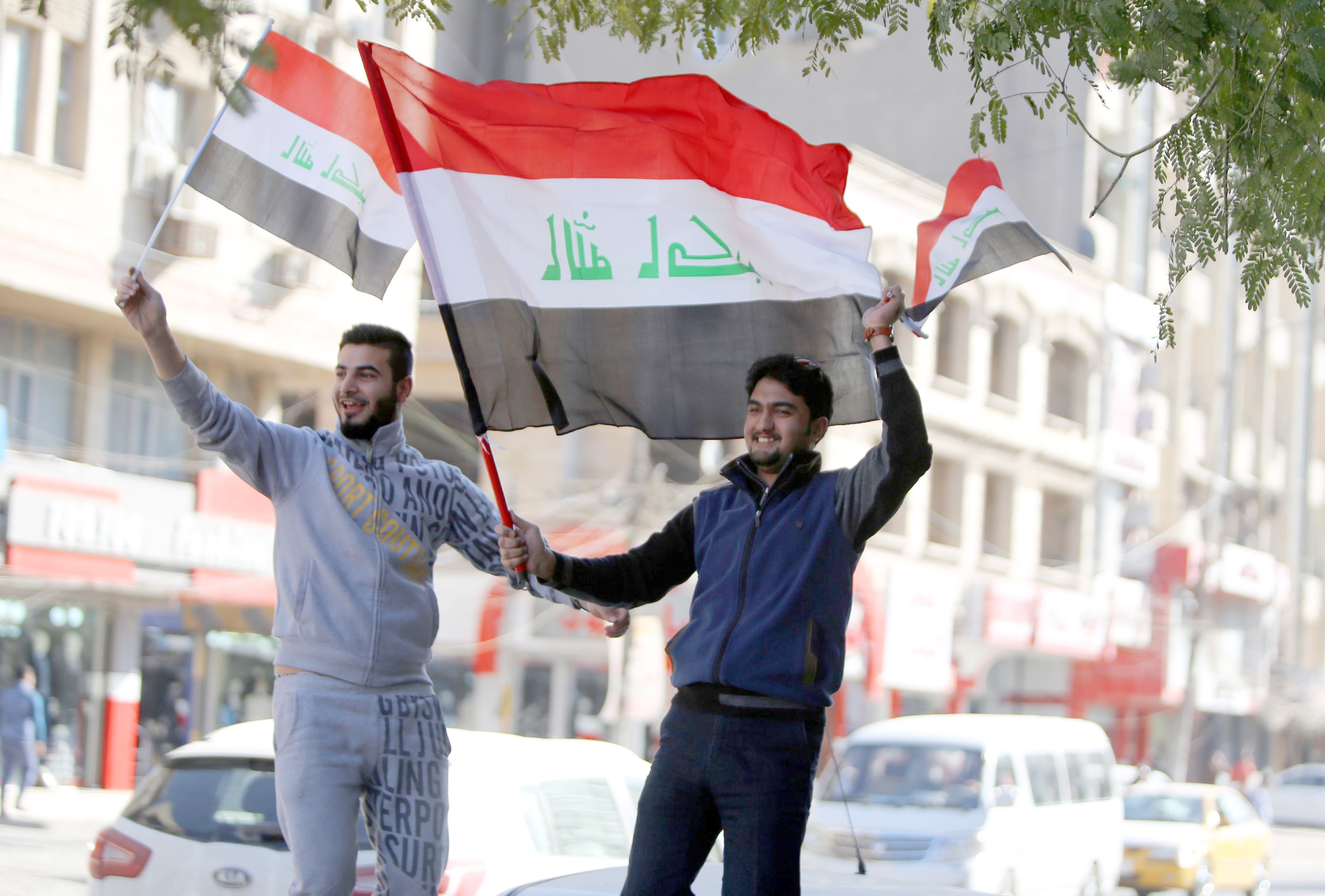Out of Iran's orbit. Iraqi men wave their national flags on the streets of Baghdad.  (AFP)