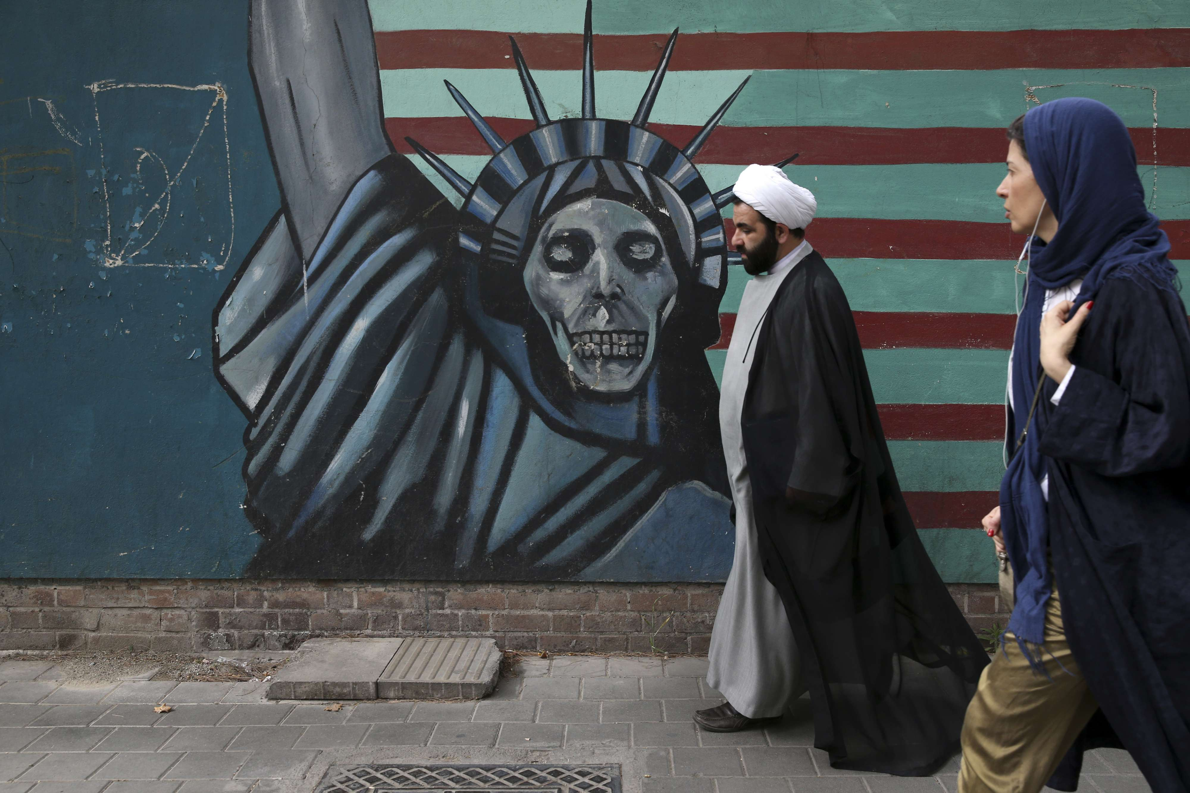 An Iranian cleric and a woman walk past an anti-US mural painted on the wall of the former US Embassy in Tehran. (AP)