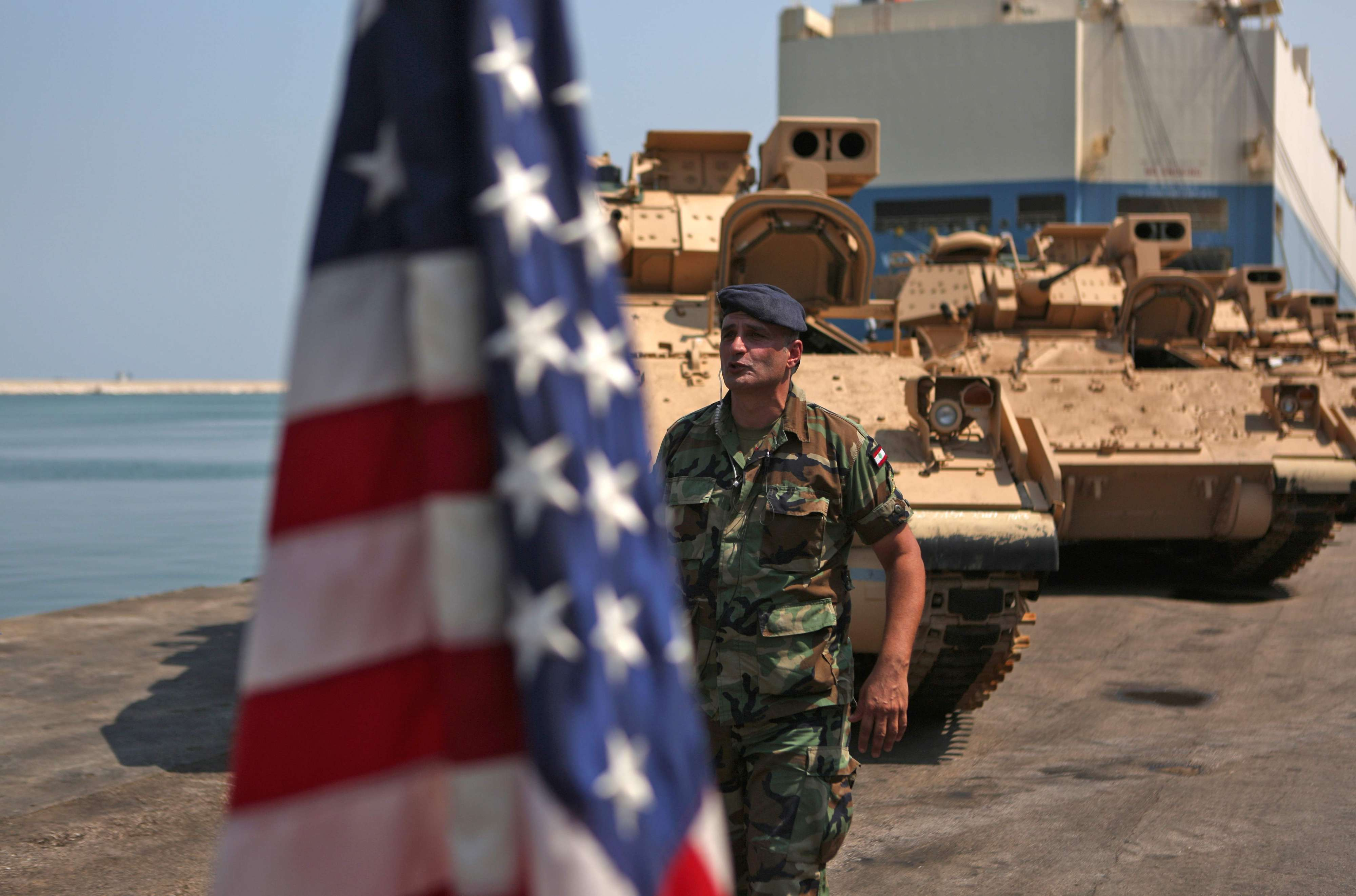 A Lebanese soldier walks past an American flag flying next to US-made Bradley Fighting Vehicles at the port of Beirut, last August. (AFP)