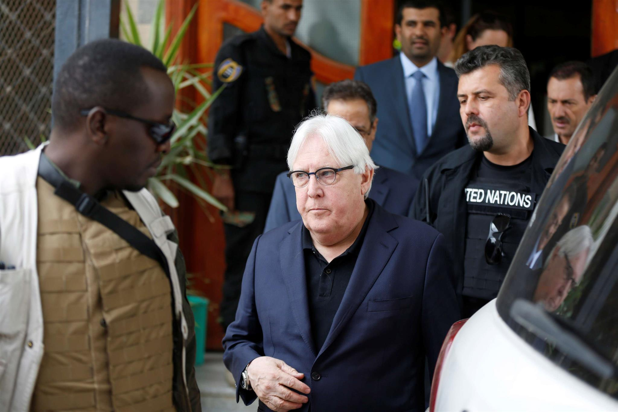 Complex task. UN Special Envoy to Yemen Martin Griffiths (C) is escorted by bodyguards as he arrives at Sana'a airport, on June 16. (Reuters)