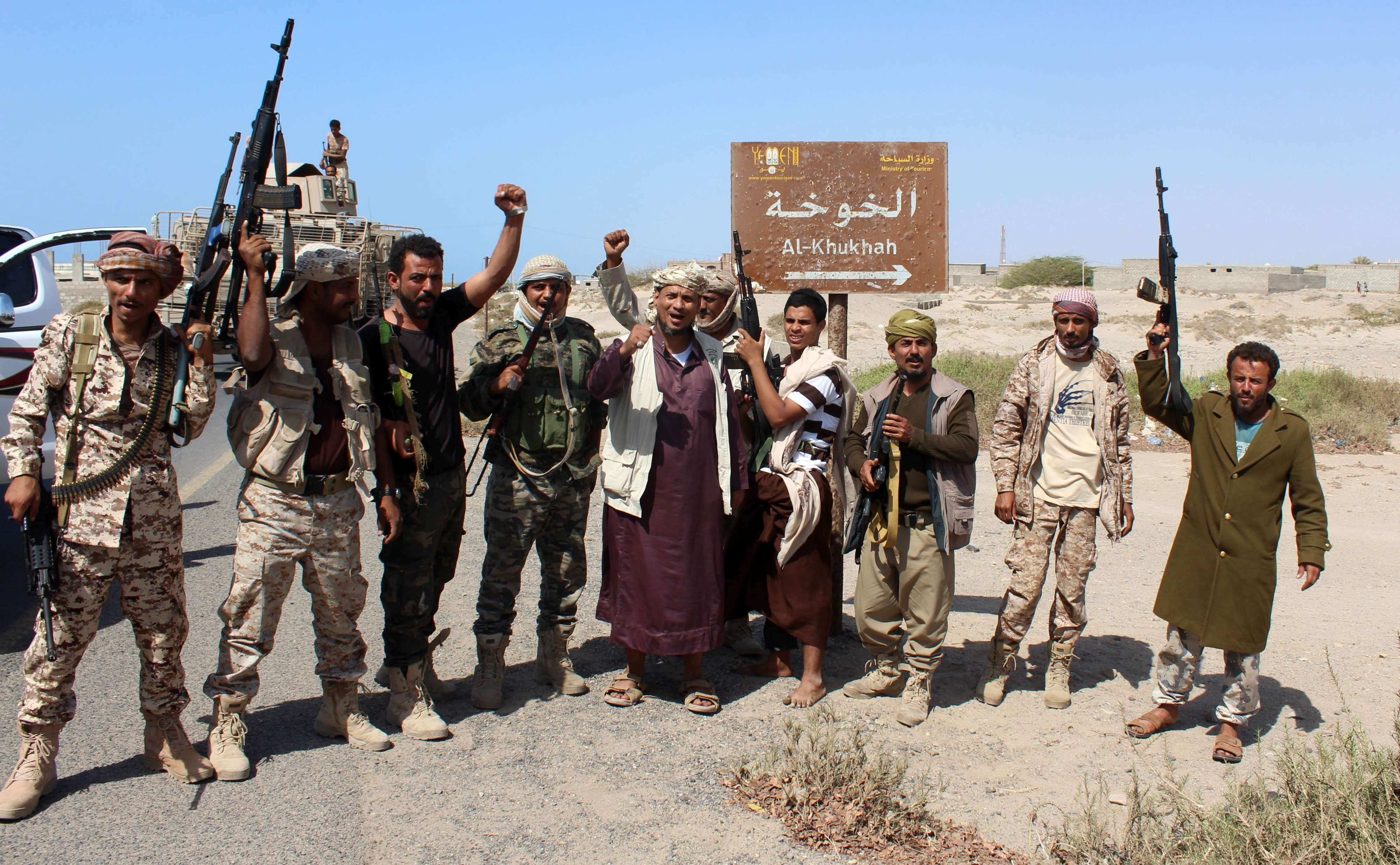 Yemeni pro-government fighters stand on a road leading to the town of Khokha, about 120km south of Hodeidah.  (AFP)