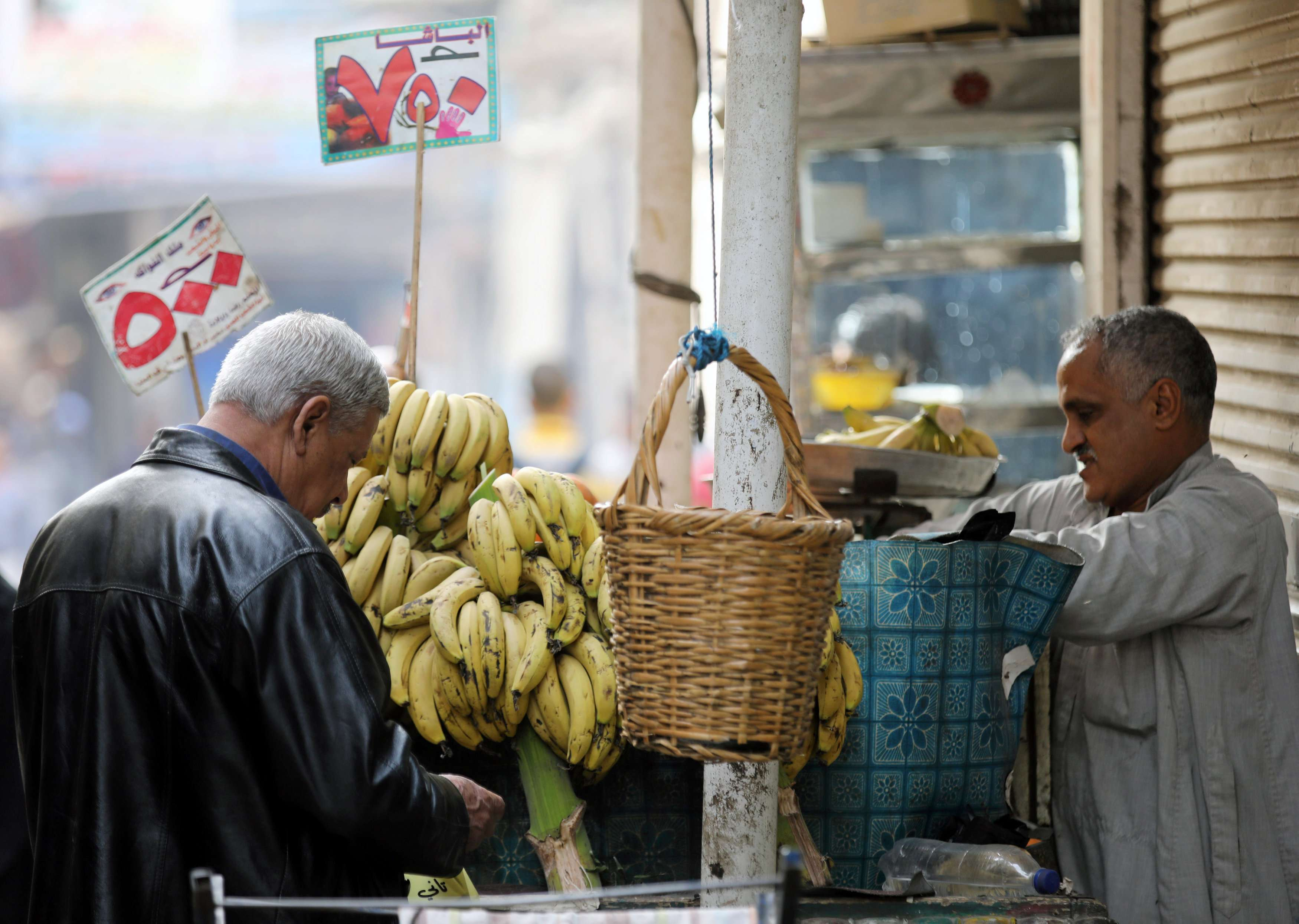 A customer counts money as he prepares to buy fruit at a market in Cairo. (Reuters)