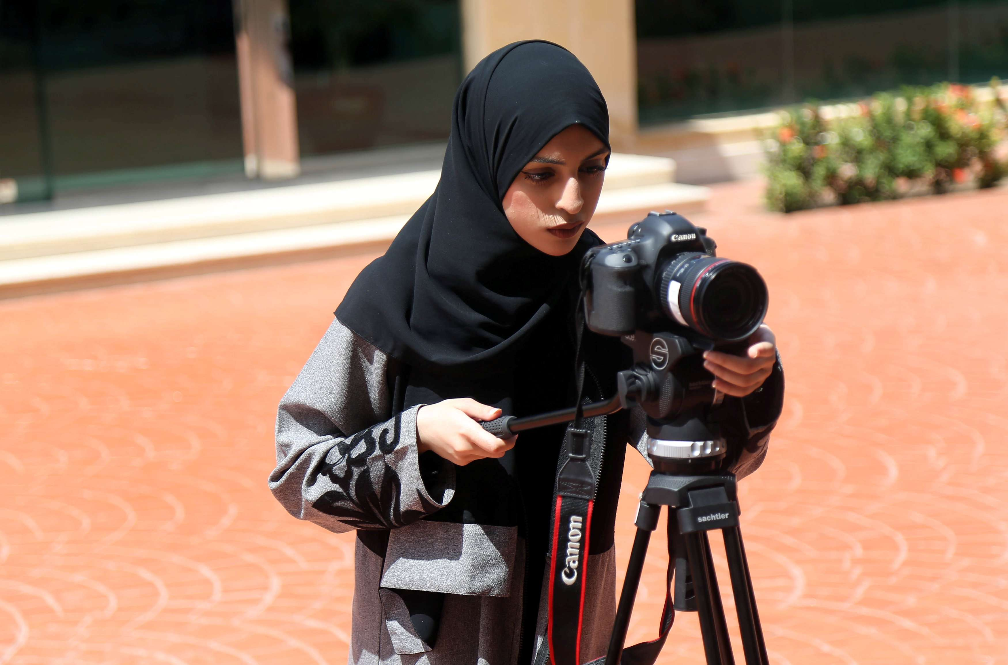 New opportunities. A Saudi woman aims a camera as she studies film-making at a university in Jeddah.      		                    (Reuters)