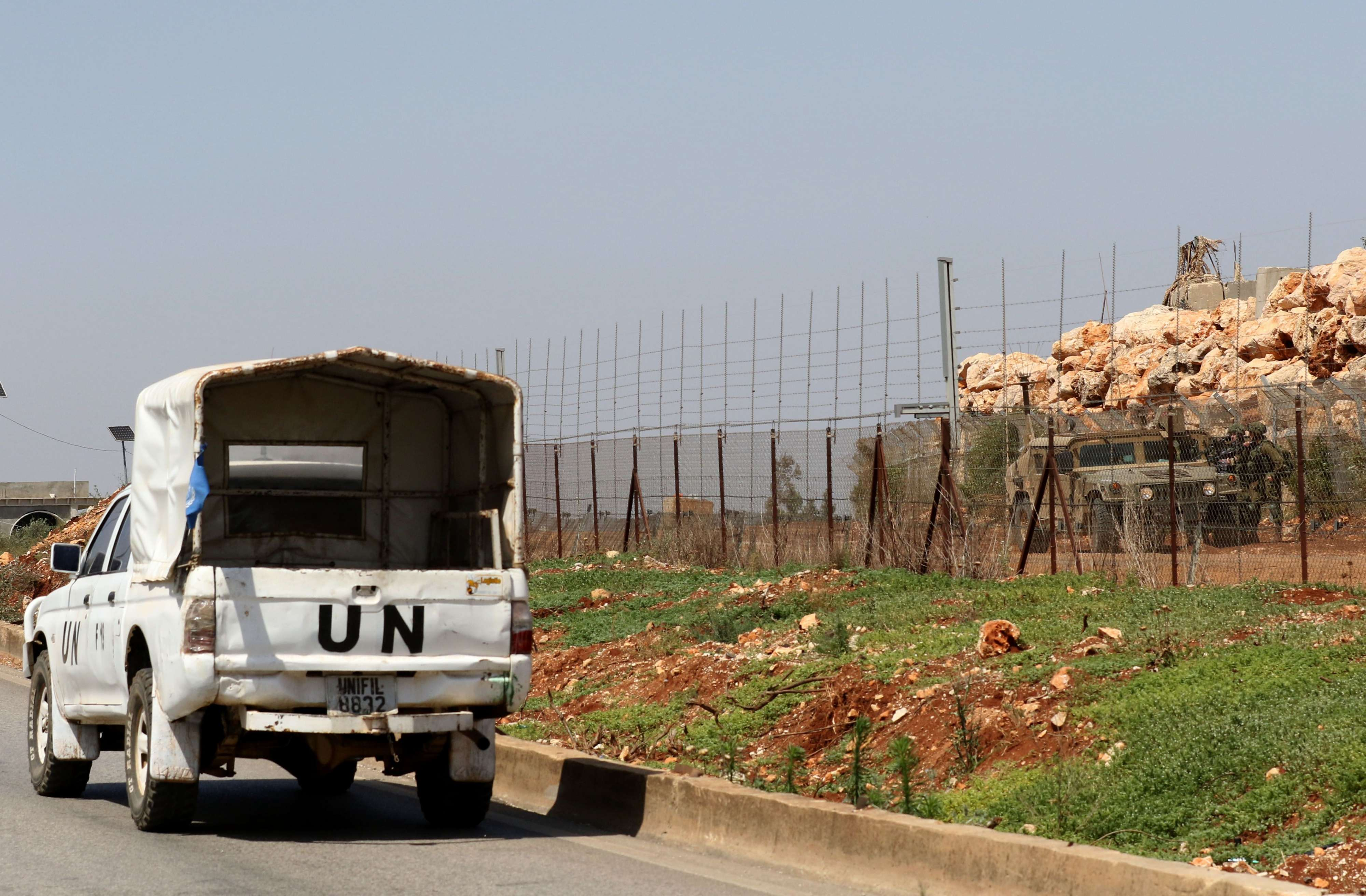 Precarious peace. A UNIFIL vehicle  drives by in south Lebanon as Israeli troops stand guard near the fence separating Lebanon from Israel, on June 8. (AFP)