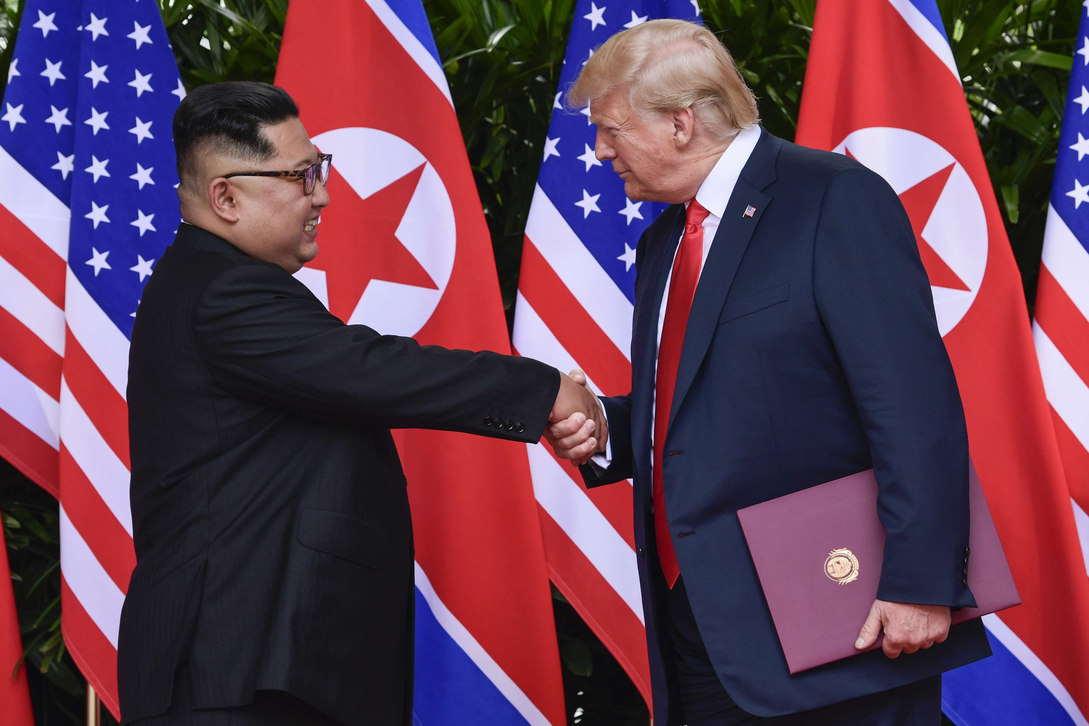 North Korean leader Kim Jong-un (L) and US President Donald Trump shake hands at the conclusion of their meetings at the Capella resort on Sentosa Island in Singapore, on June 12. (AP)