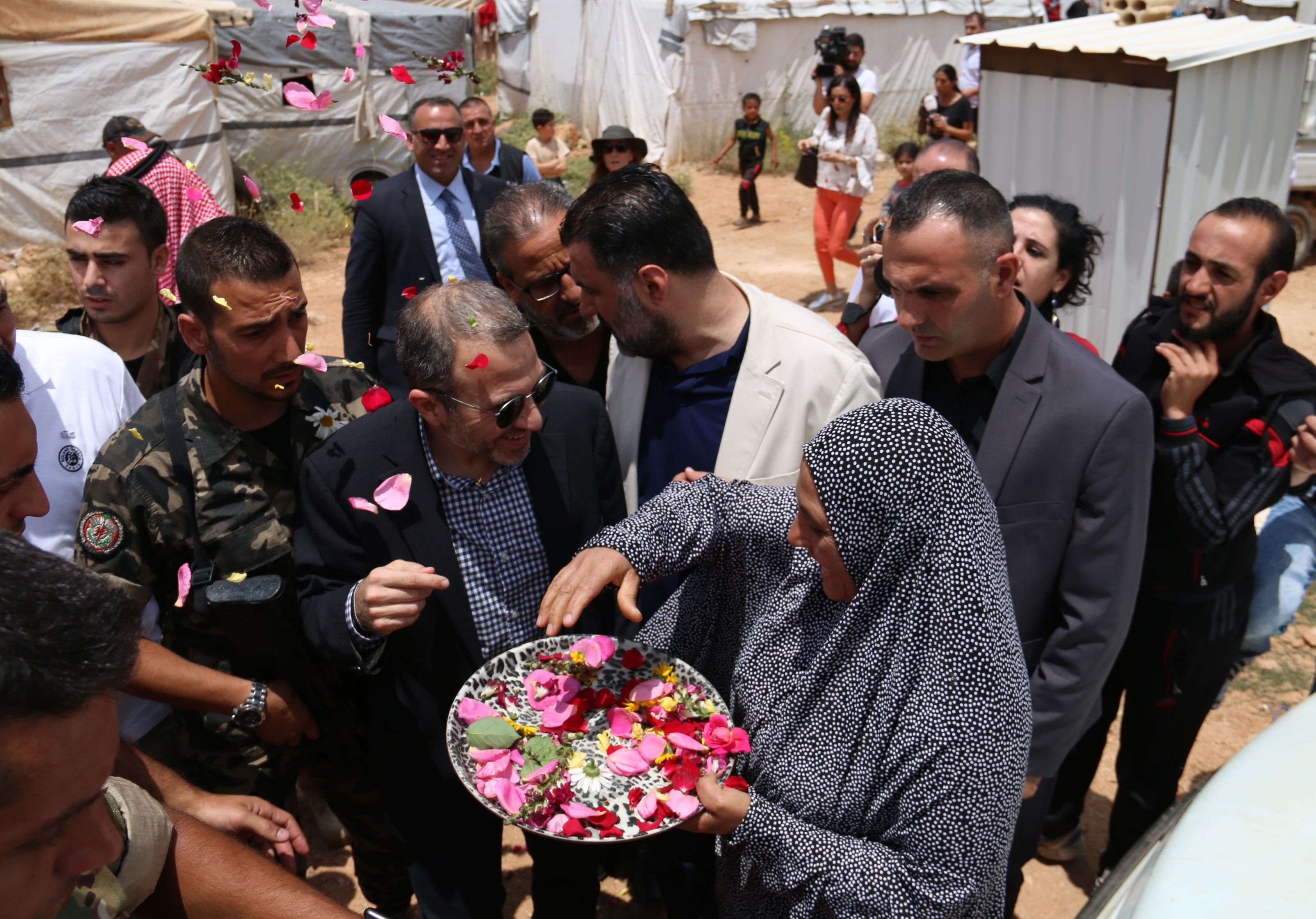 Lebanese Minister of Foreign Affairs and Expatriation Gebran Bassil (C) is greeted with flower petals at a Syrian refugee camp in the town of Arsal on the eastern border with Syria, on June 13, 2018. (AFP)