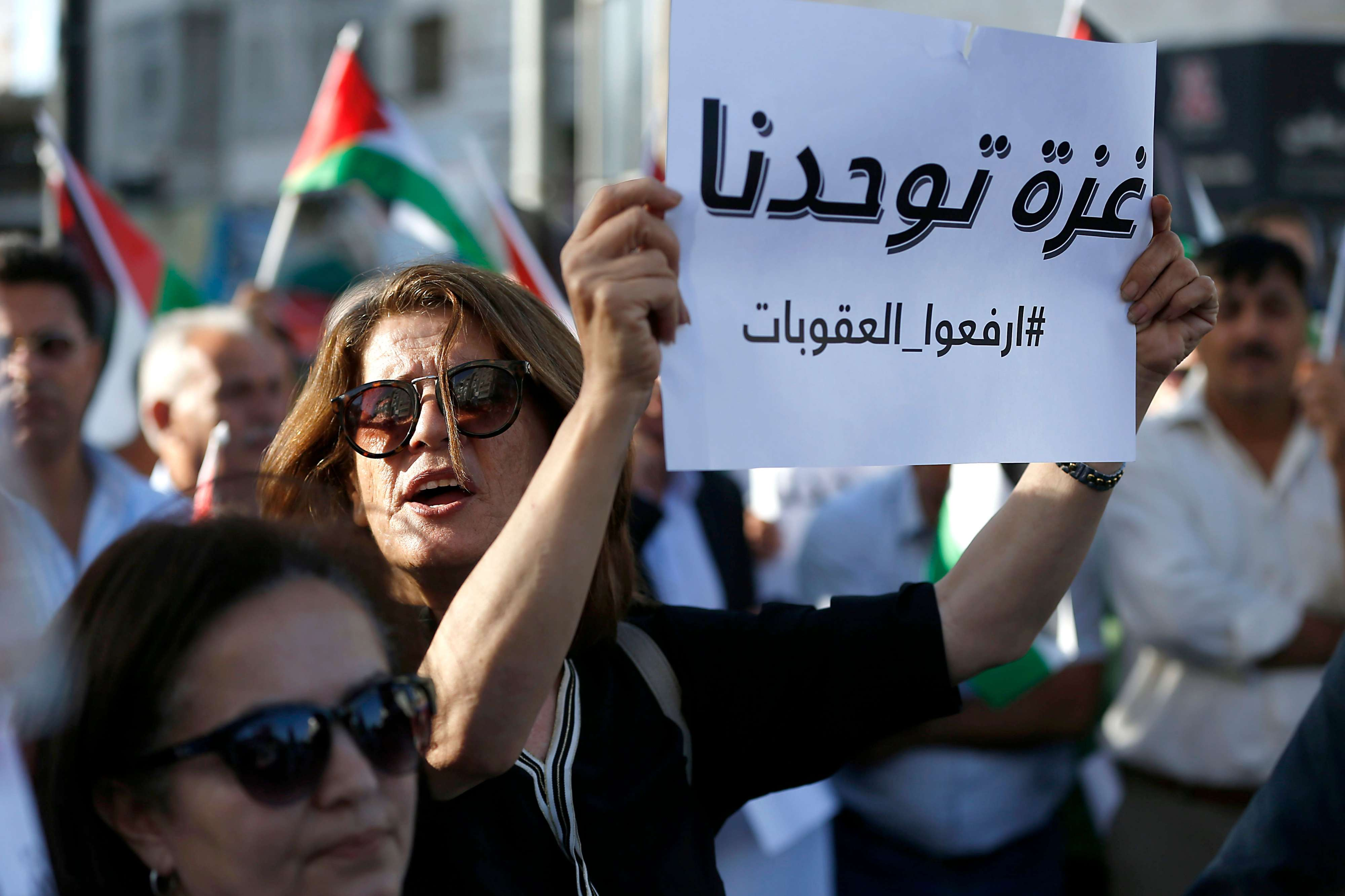 "Indispensable but elusive unity. A Palestinian woman holds a banner reading ""Gaza unites us, lift the sanctions"" as she takes part in a protest in the occupied West Bank city of Ramallah, on June 23. (AFP)"