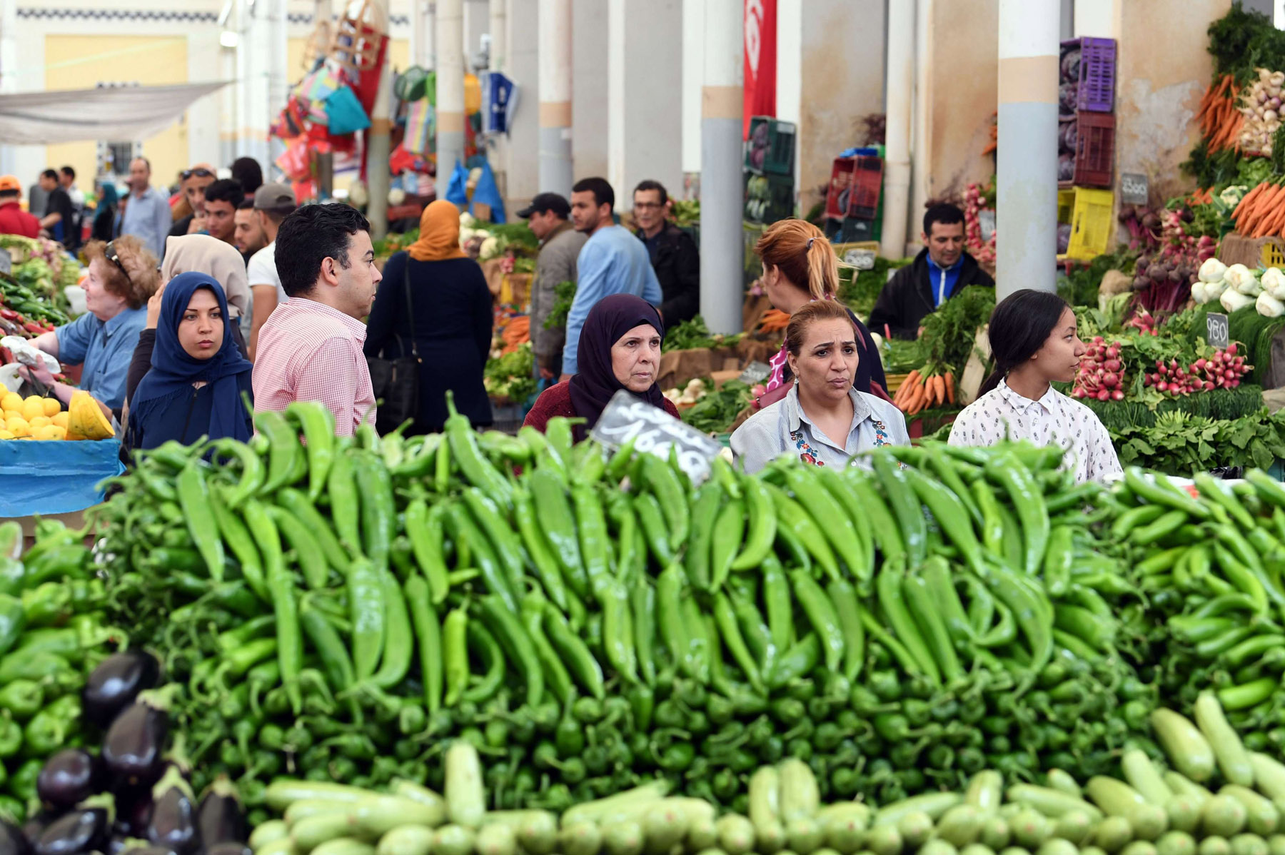 A squeeze on consumers. Tunisians walk at a vegetables and fruit market in Tunis.                           (AFP)