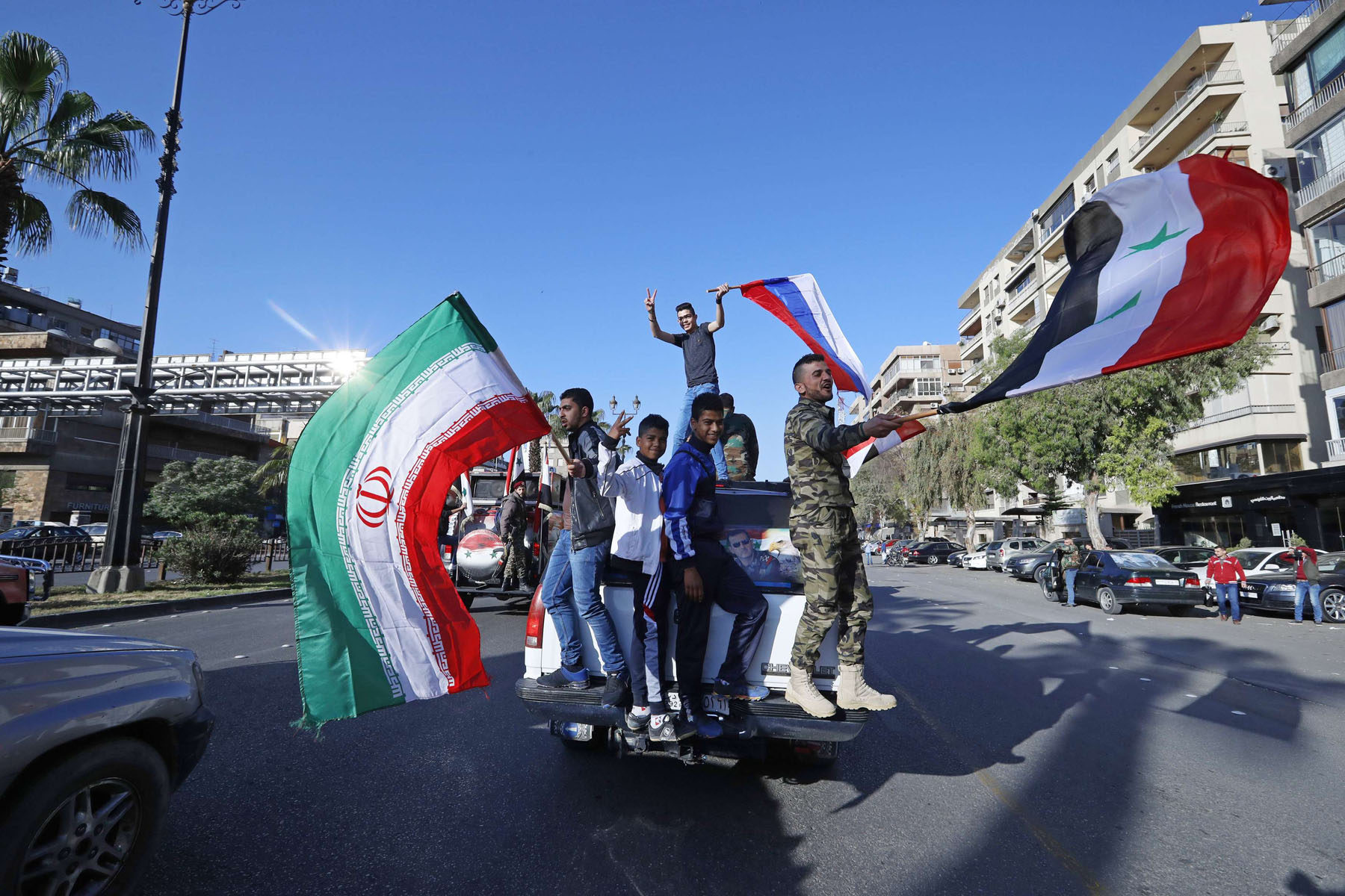 Reality on the ground. Syrian government supporters wave  Syrian, Iranian and Russian flags as they chant slogans against US President Trump in Damascus, last April.  (AP)