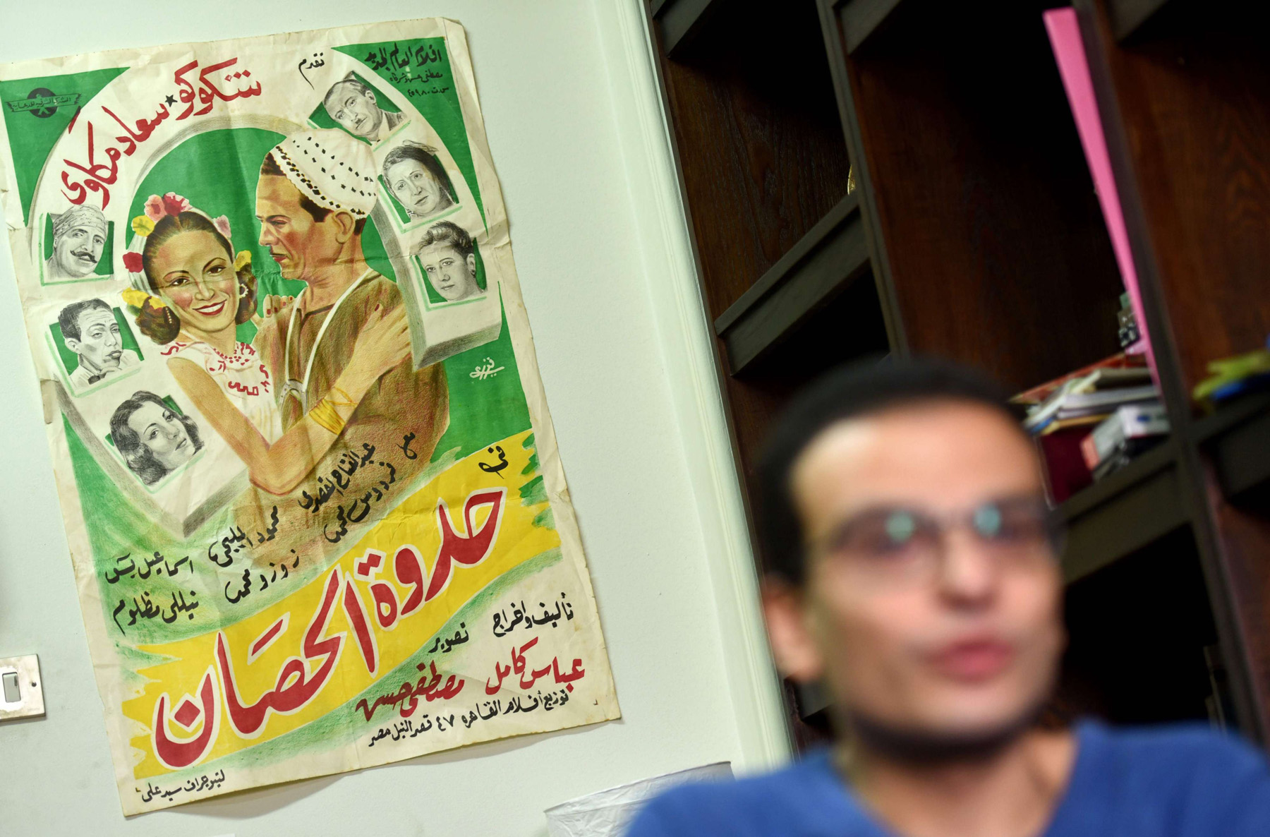 Through the eyes of men. An Egyptian man sits in front of a vintage cinema poster in Cairo.                       (AFP)