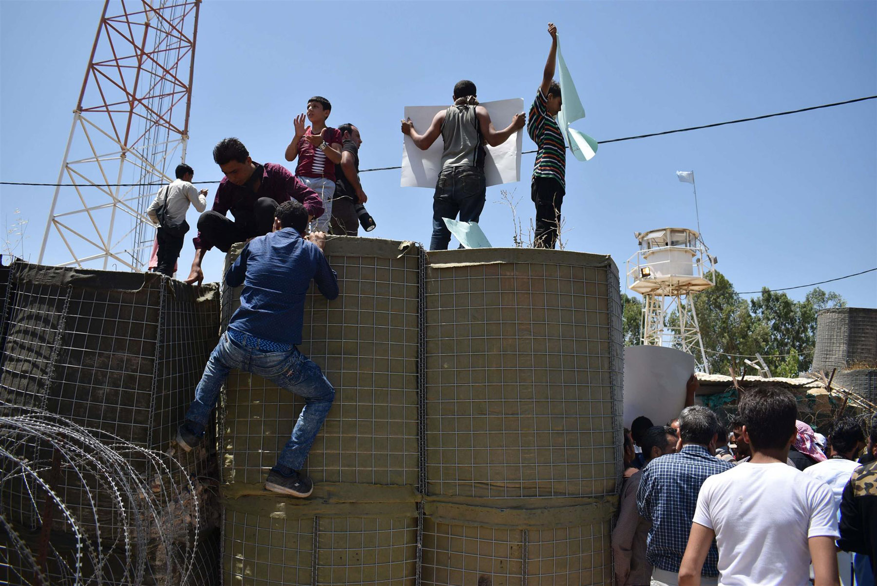 Desperate measures. Displaced Syrians climb fences and hold signs during a protest in front of a UN base in the province of Quneitra near the border with the Israeli-occupied Golan Heights, on July 4.  (AFP)