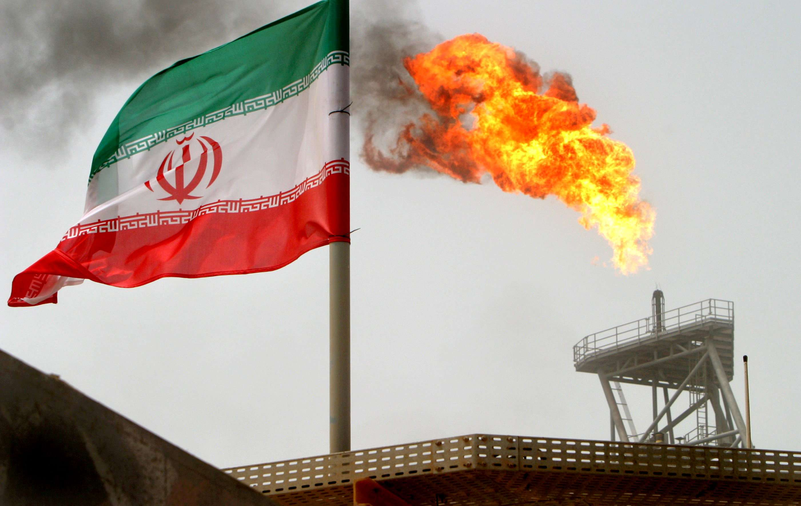 Tighter screws. A gas flare on an oil production platform in the Soroush oil fields is seen alongside an Iranian flag in the Arabian Gulf. (Reuters)