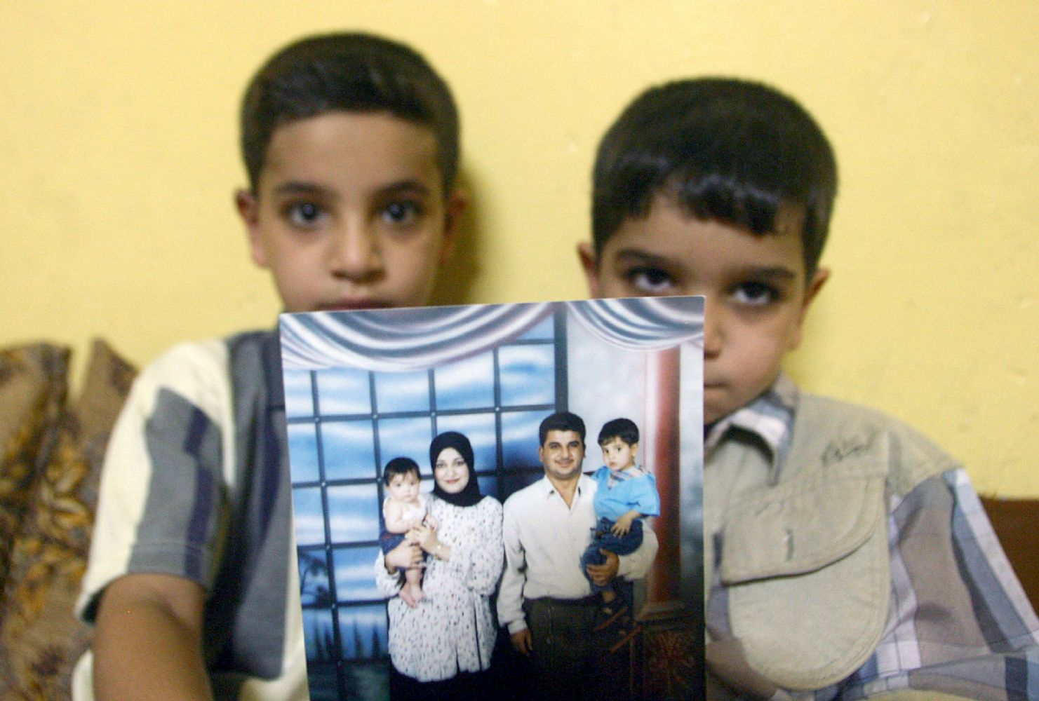 A file picture of Baha Mousa's sons as they show off a family photo of them posing with their father and mother at their home in Basra. (AFP)