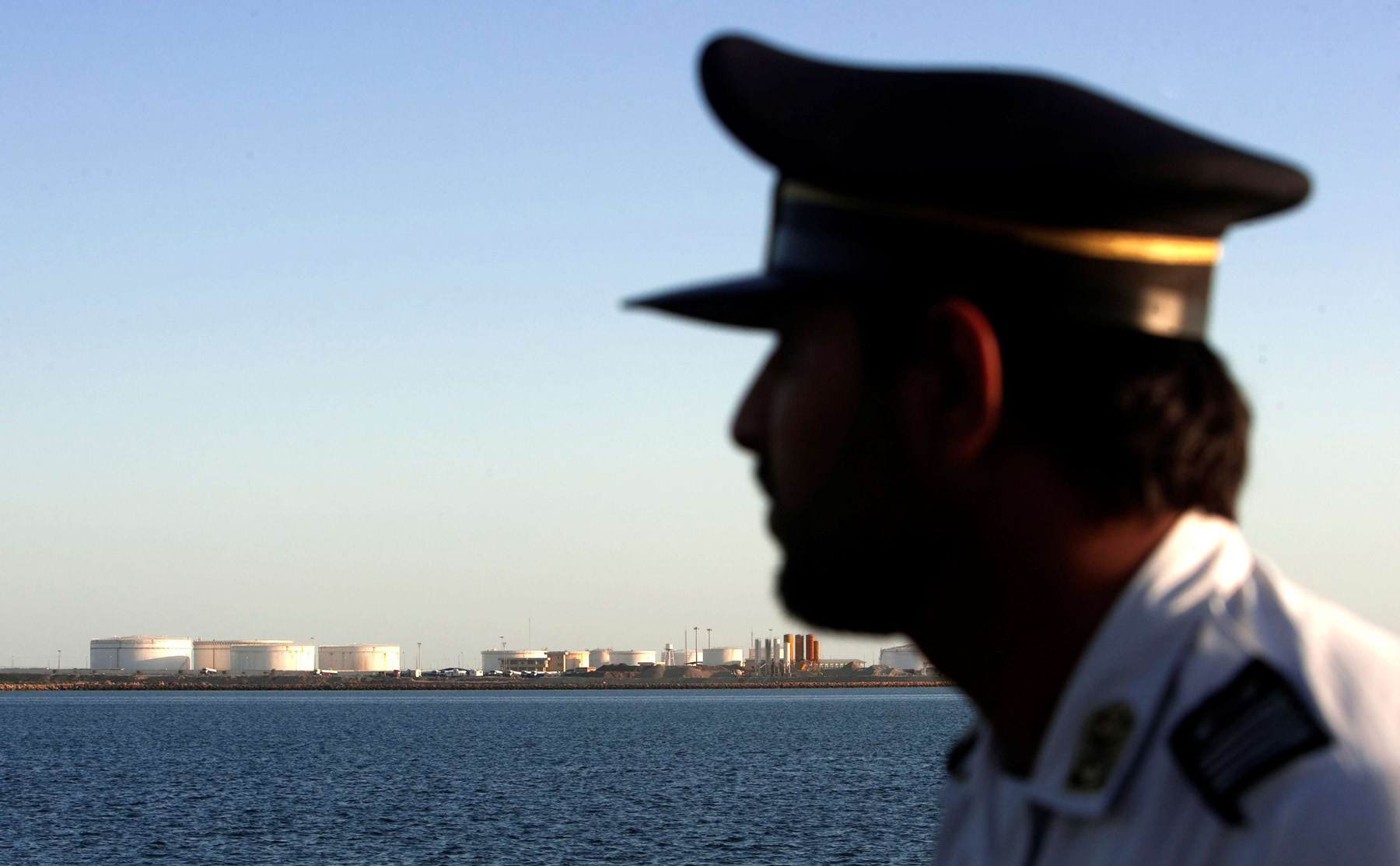 Bargaining chip. An Iranian security personnel looks on at oil docks at the port of Kalantari, east of the Strait of Hormuz. (Reuters)