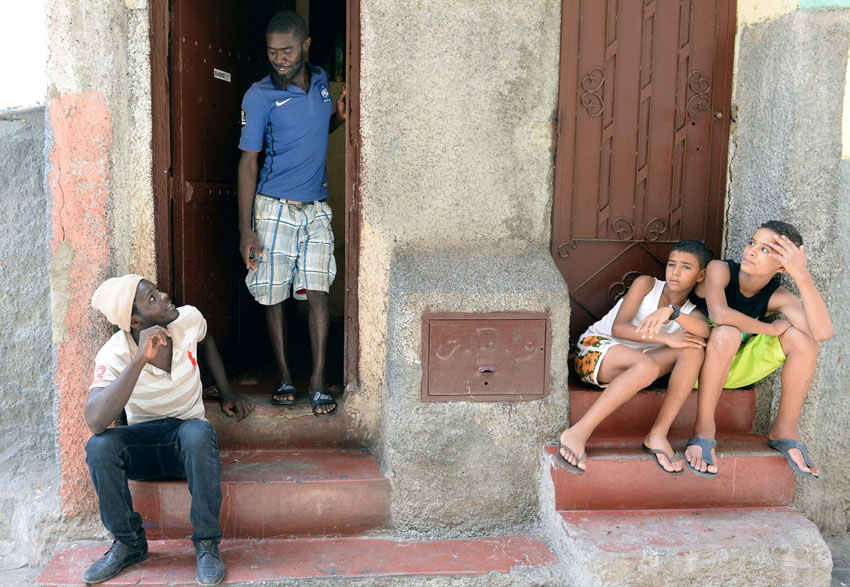 Inconvenient conditions. Senegalese immigrants and Moroccan children sitting in front of a building in the Takaddum neighbourhood of Rabat.                                                                        (AFP)