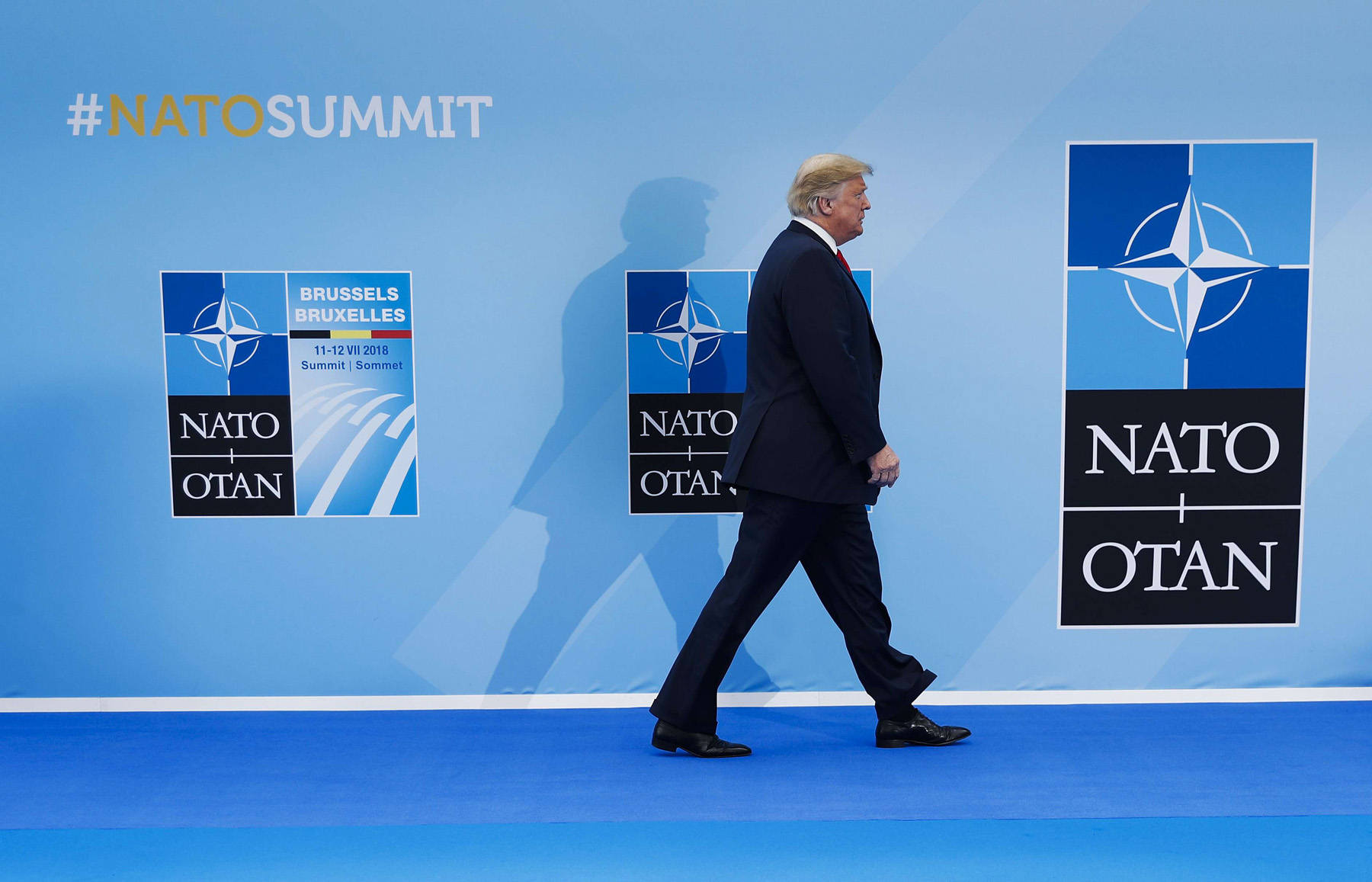 Odd man out. US President Donald Trump walks in as he is introduced at the summit of heads of state and government at NATO headquarters in Brussels, on July 11. (AP)