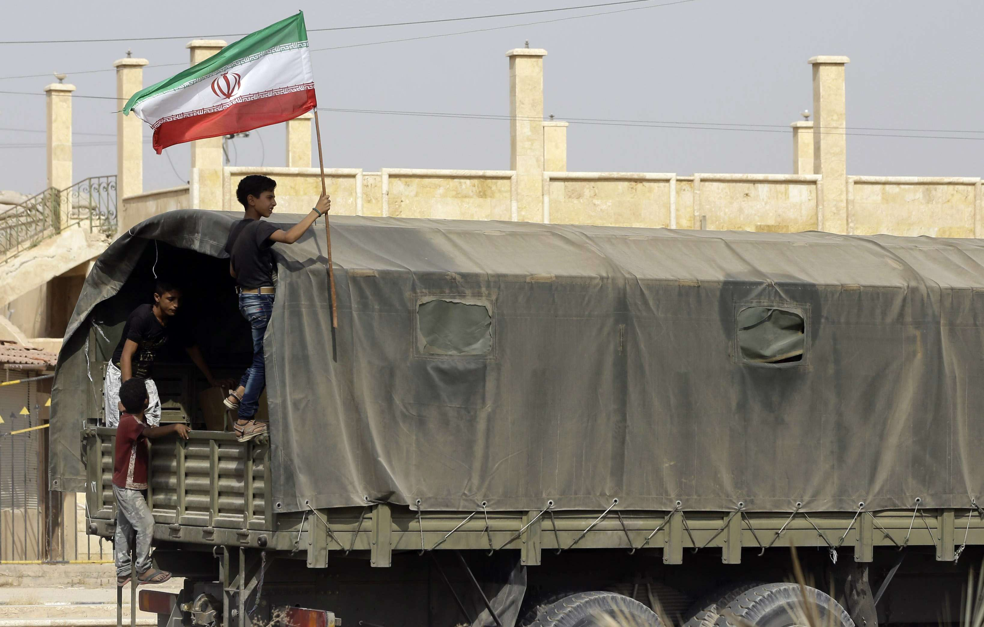 A Syrian boy holds the Iranian flag as a truck carrying aid provided by Iran arrives in the eastern city of Deir Ez-Zor, last September. (AFP)