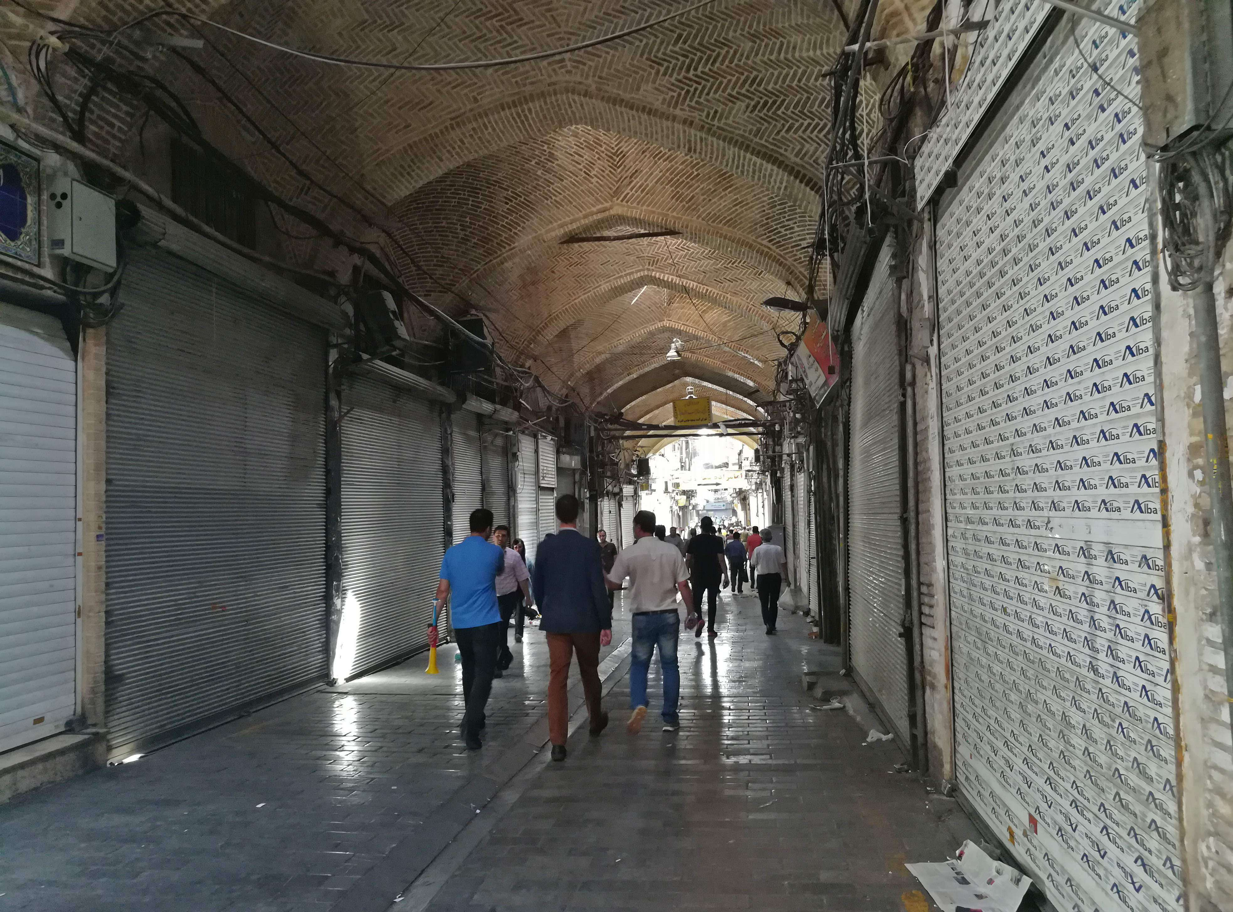 Iranians walk through the old grand bazaar where shops are closed after a protest, in Tehran, on June 25. (AFP)