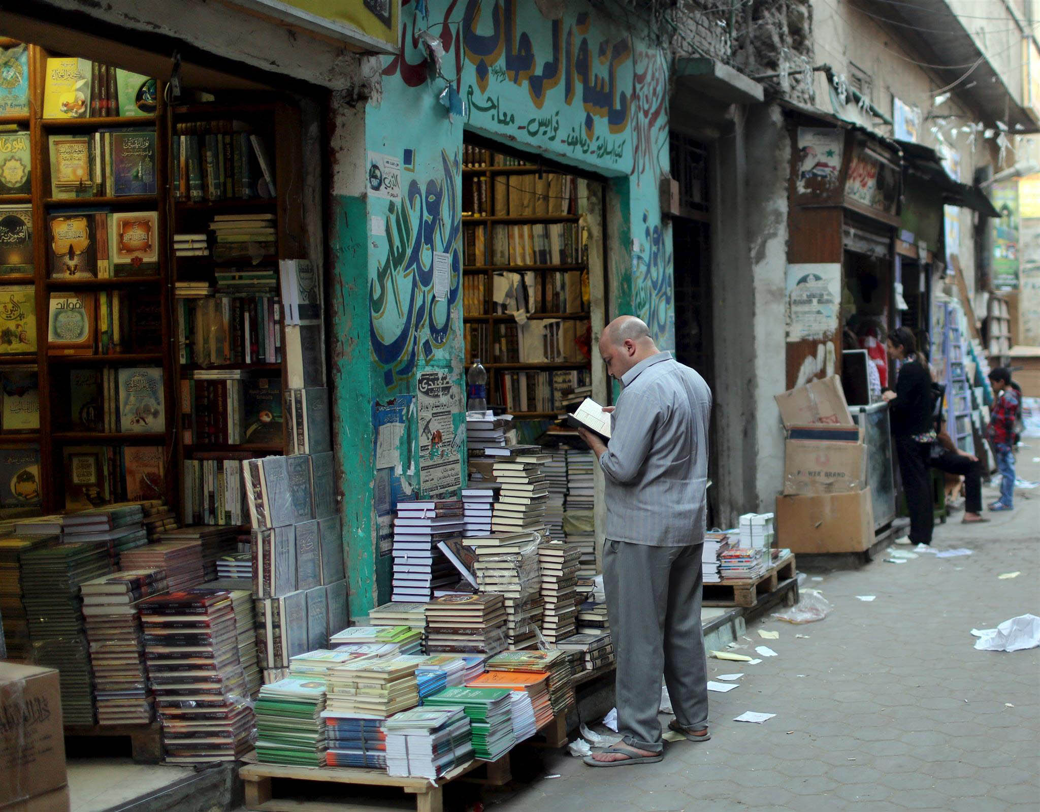 Ongoing problem. A man reads outside a bookshop that sells Islamic and reference books for al-Azhar students near the al-Azhar Mosque in Cairo.       (AP)